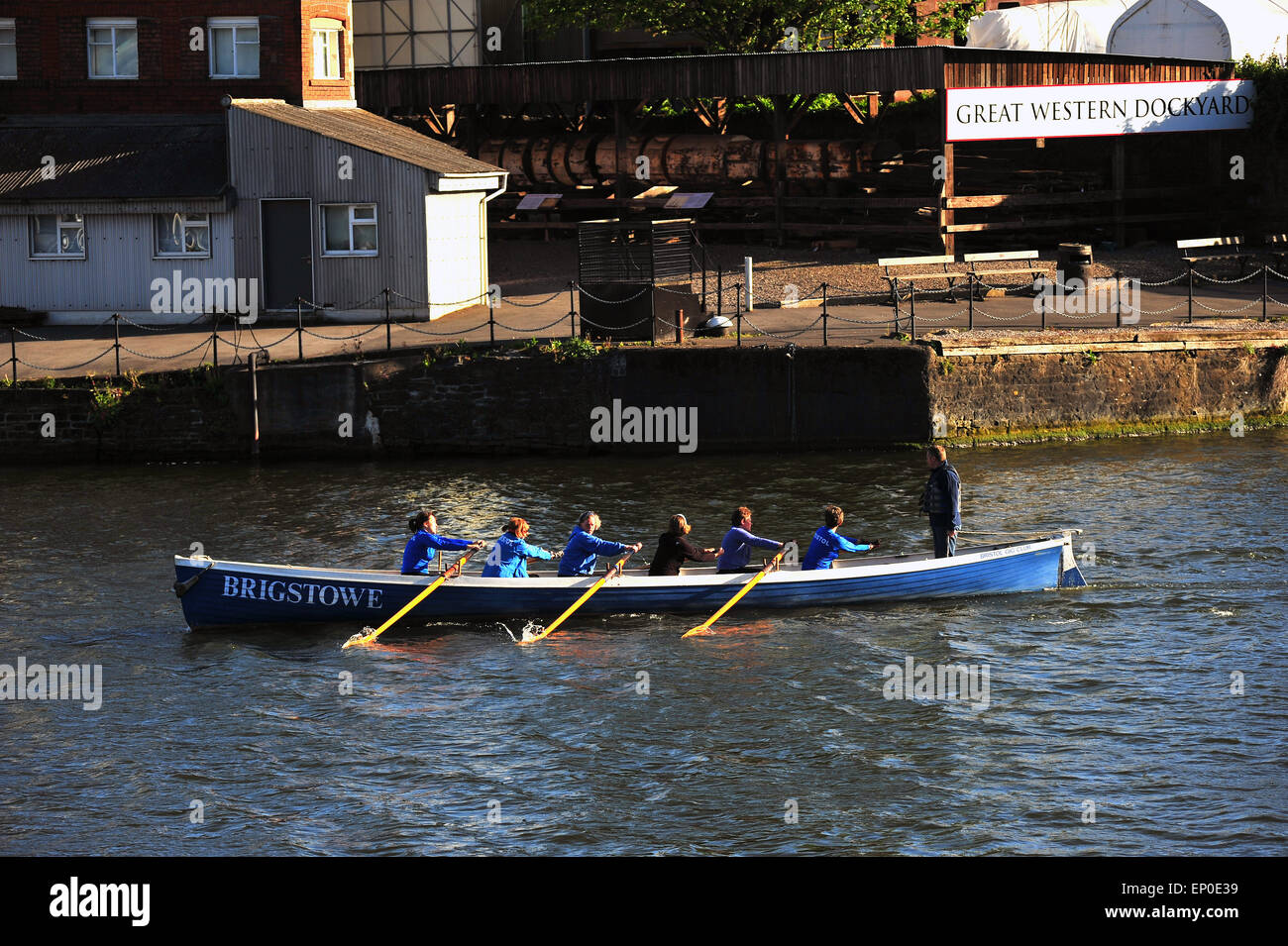 Bristol, UK. 12th May, 2015. Weather: Female rowers row through Bristol harbour with the SS Great Britain in the - Stock Image