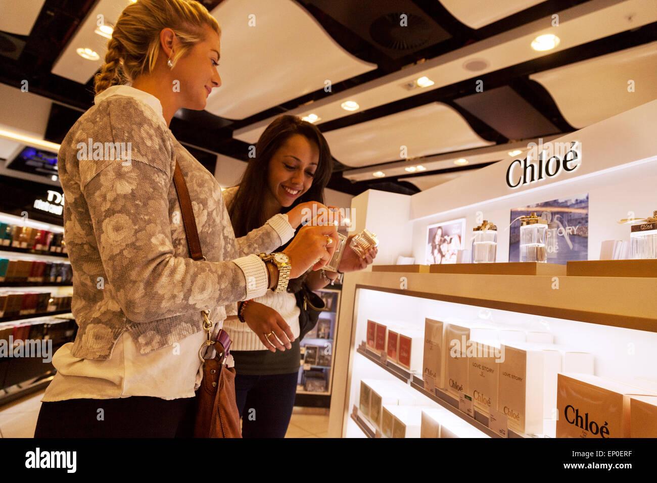 Two young women duty free shopping for perfume, the duty-free shop, South Terminal, Gatwick airport London UK Stock Photo