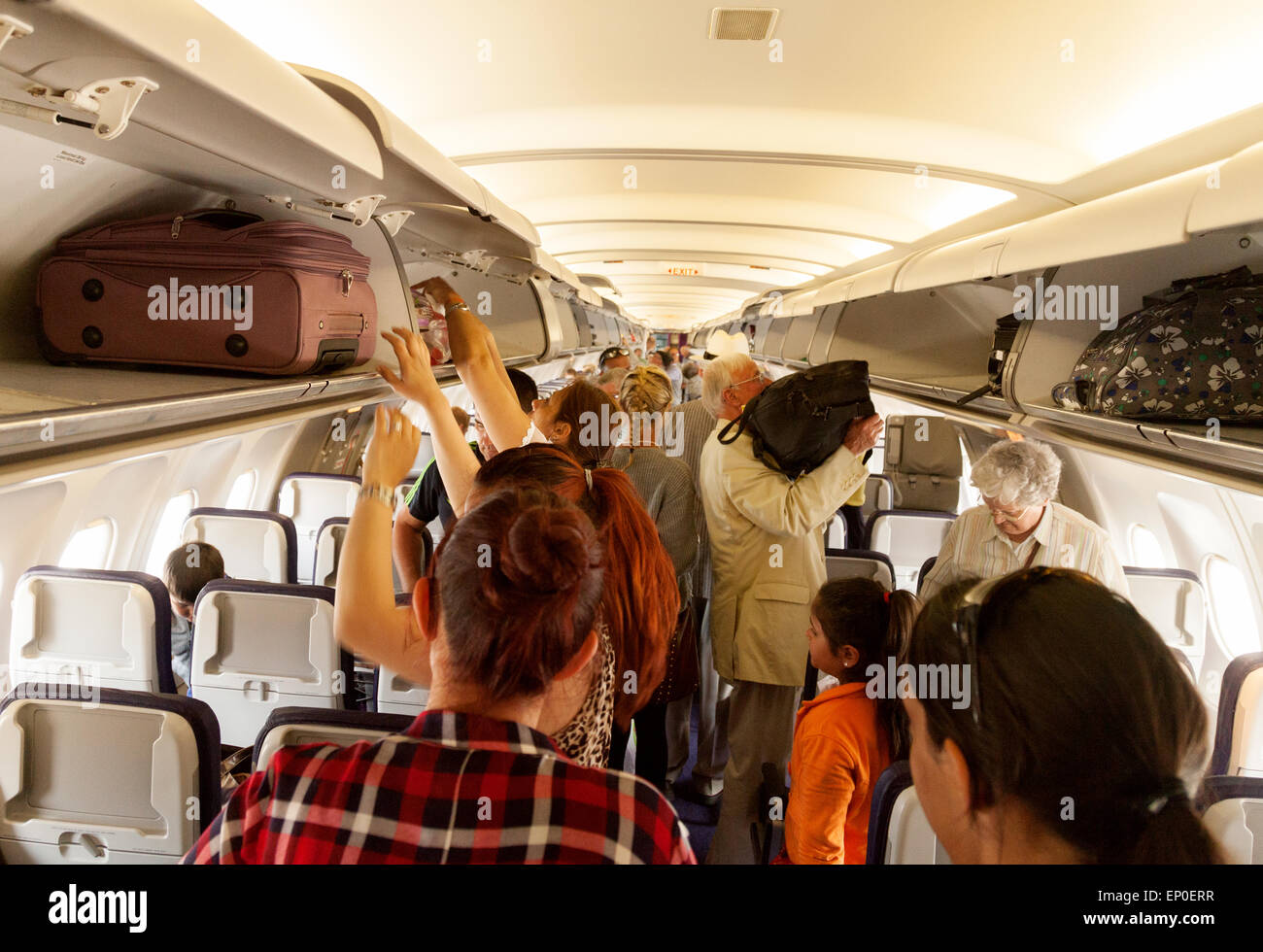 Airplane passengers ion a flight with Monarch Airlines in the cabin storing hand luggage in the overhead lockers - Stock Image