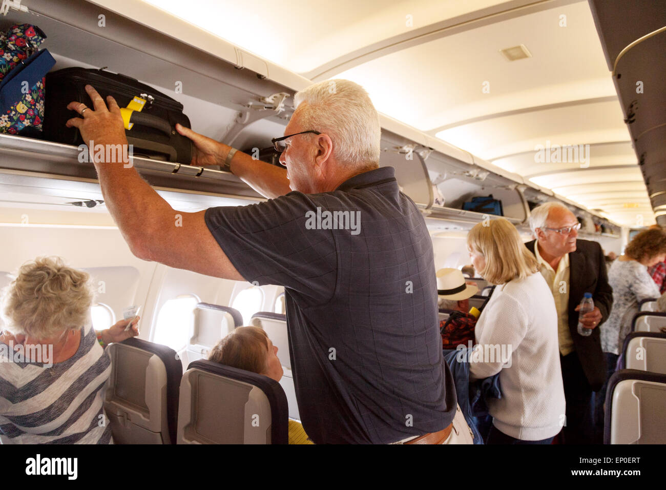 A plane passenger storing hand luggage in the overhead locker on a Monarch Airlines flight from Madeira to Gatwick Stock Photo