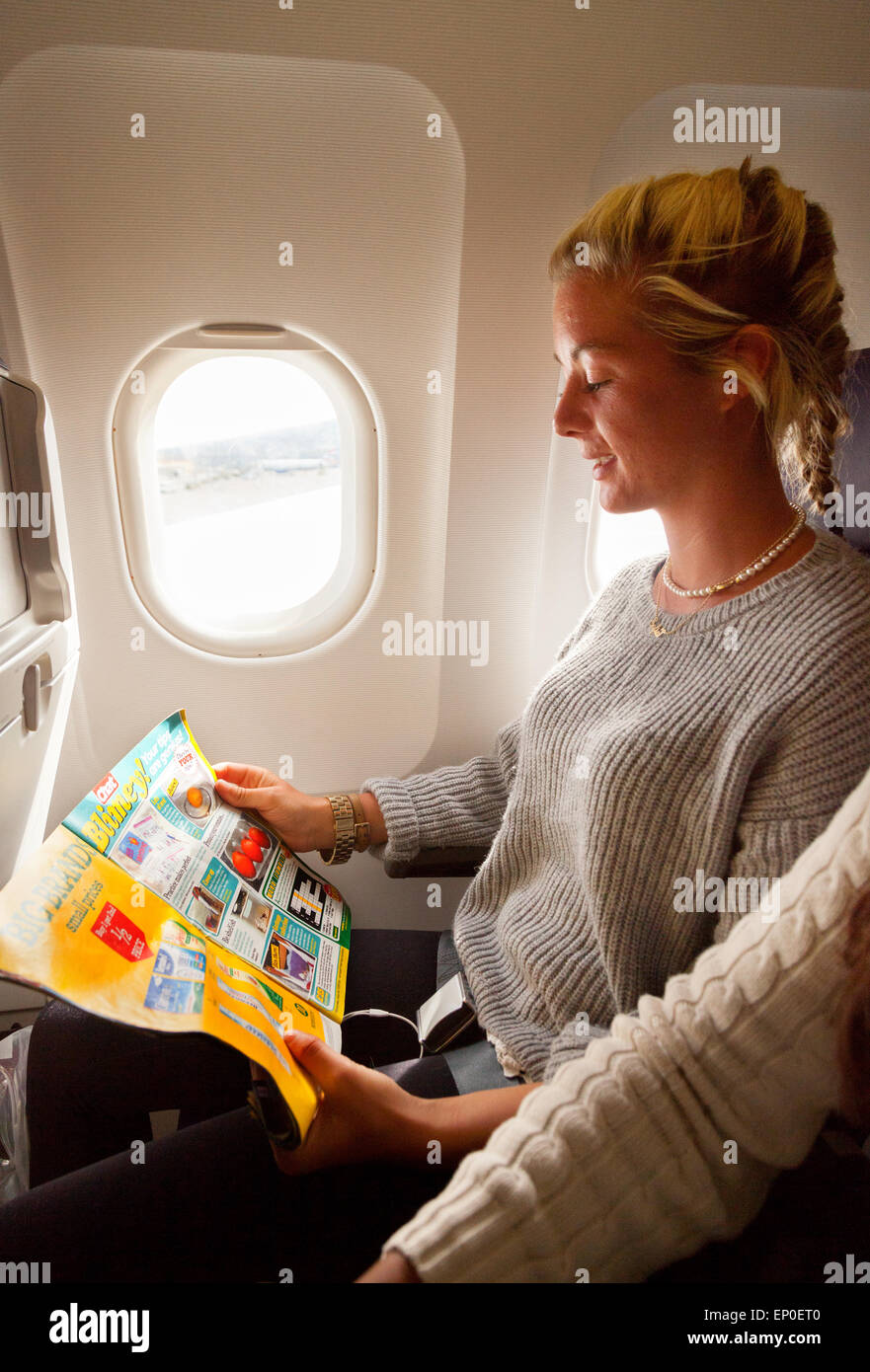 A Young Woman Sitting In Her Airplane Window Seat Reading
