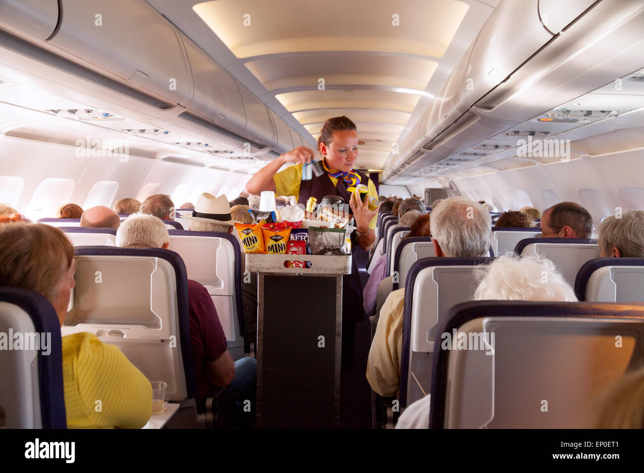 A flight attendant member of the cabin crew serving food on a Monarch Airlines airplane from Madeira to Gatwick - Stock Image