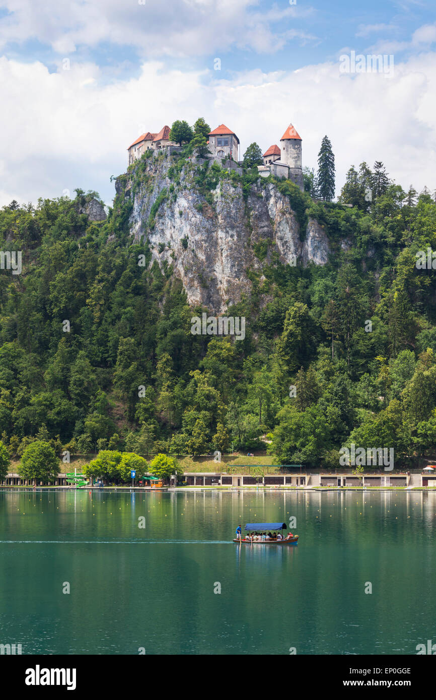 Lake Bled, Upper Carniola, Slovenia.  Bled Castle seen across the lake. Tourists enjoying boating excursion. Stock Photo