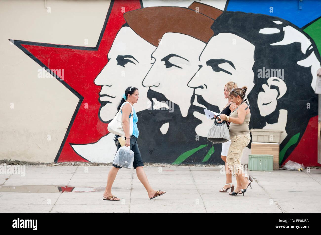 HAVANA, CUBA - JUNE 13, 2011: Cuban pedestirans walk in front of propaganda mural featuring three leaders of the - Stock Image