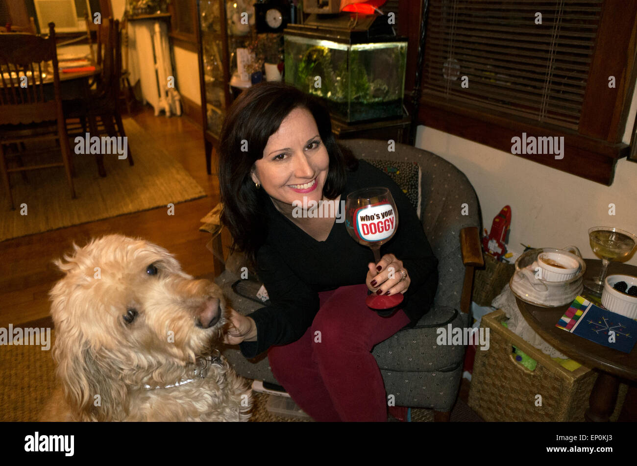 Woman displaying her 'Who's Your Doggy' wine glass with her Goldendoodle dog Gunnar at her birthday. - Stock Image