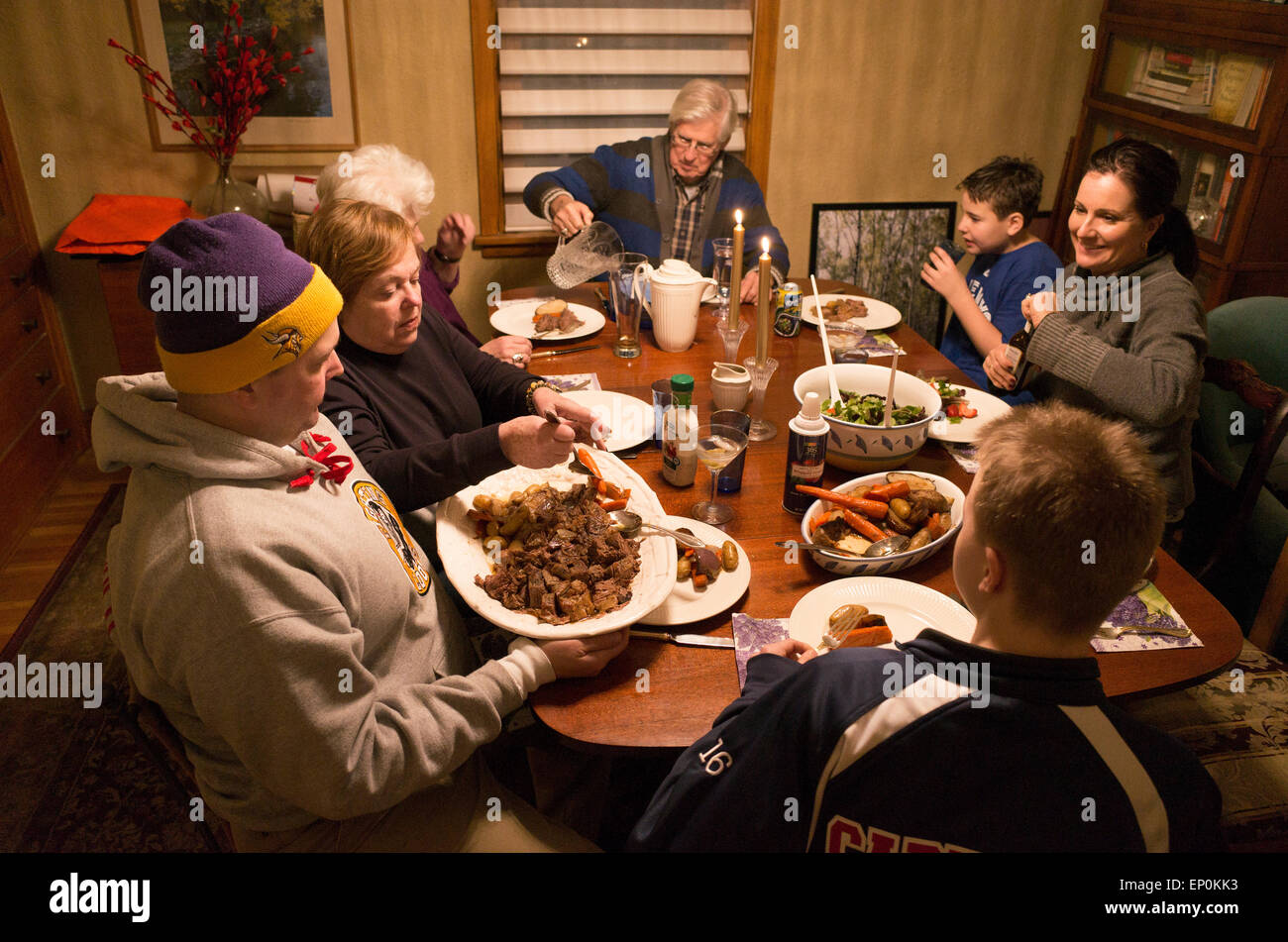 Family of three generations enjoying a hearty beef and vegetable dinner. St Paul Minnesota MN USA - Stock Image