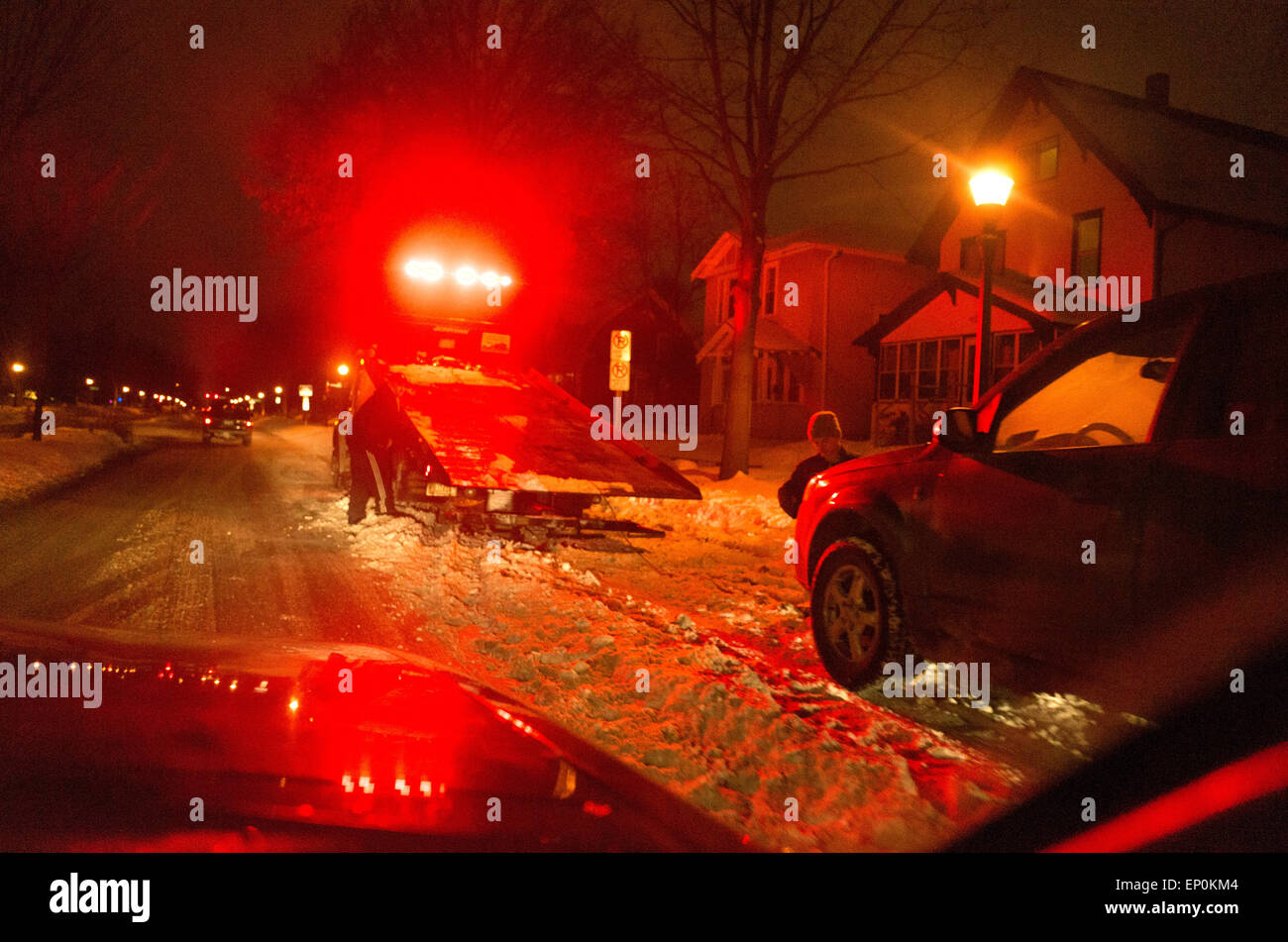 Tow truck ready to pick up illegally parked car at night after winter snowfall. St Paul Minnesota MN USA - Stock Image