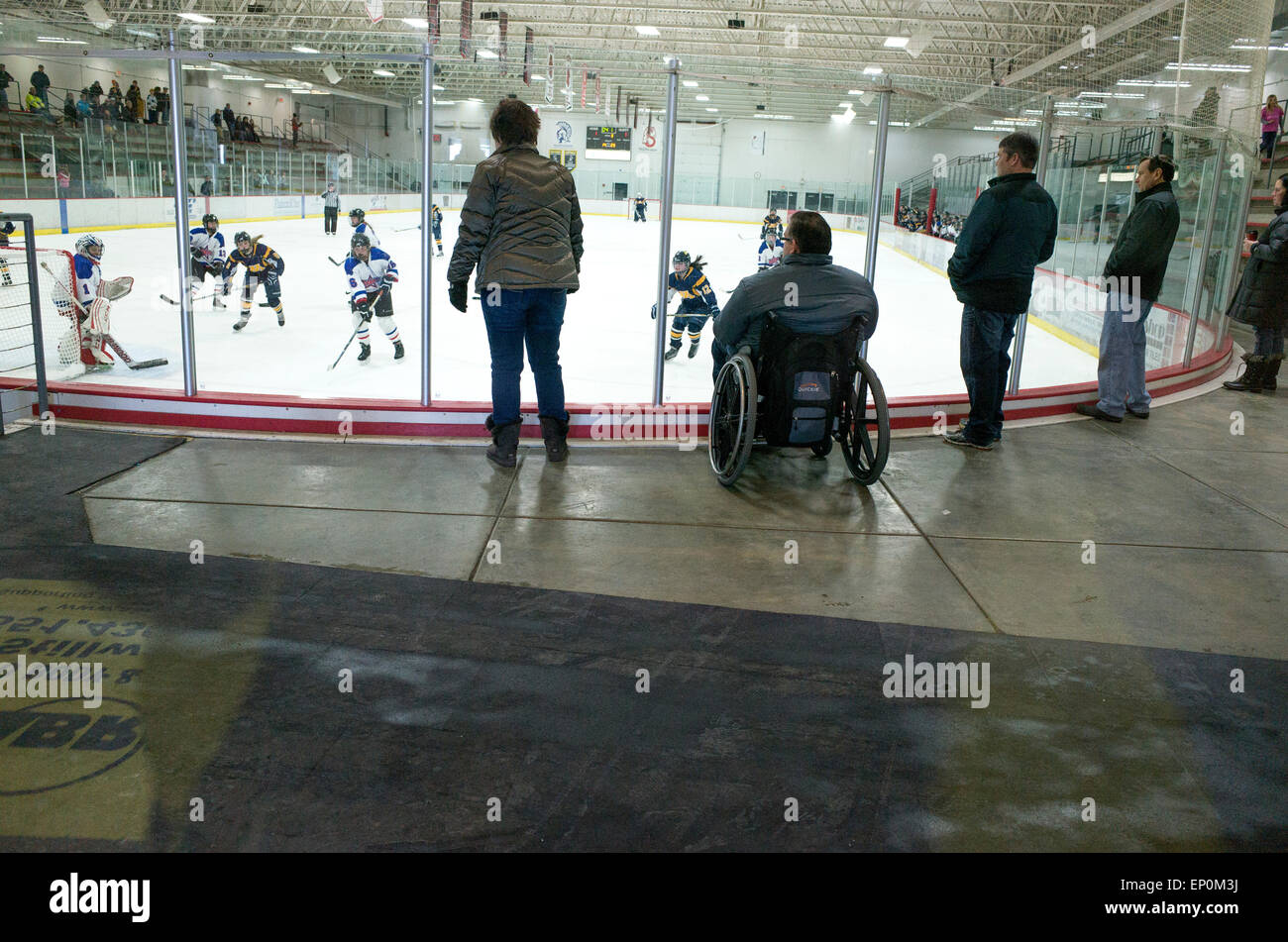 Handicapped man in wheelchair with easy access watching girls hockey game. Stillwater Minnesota MN USA - Stock Image