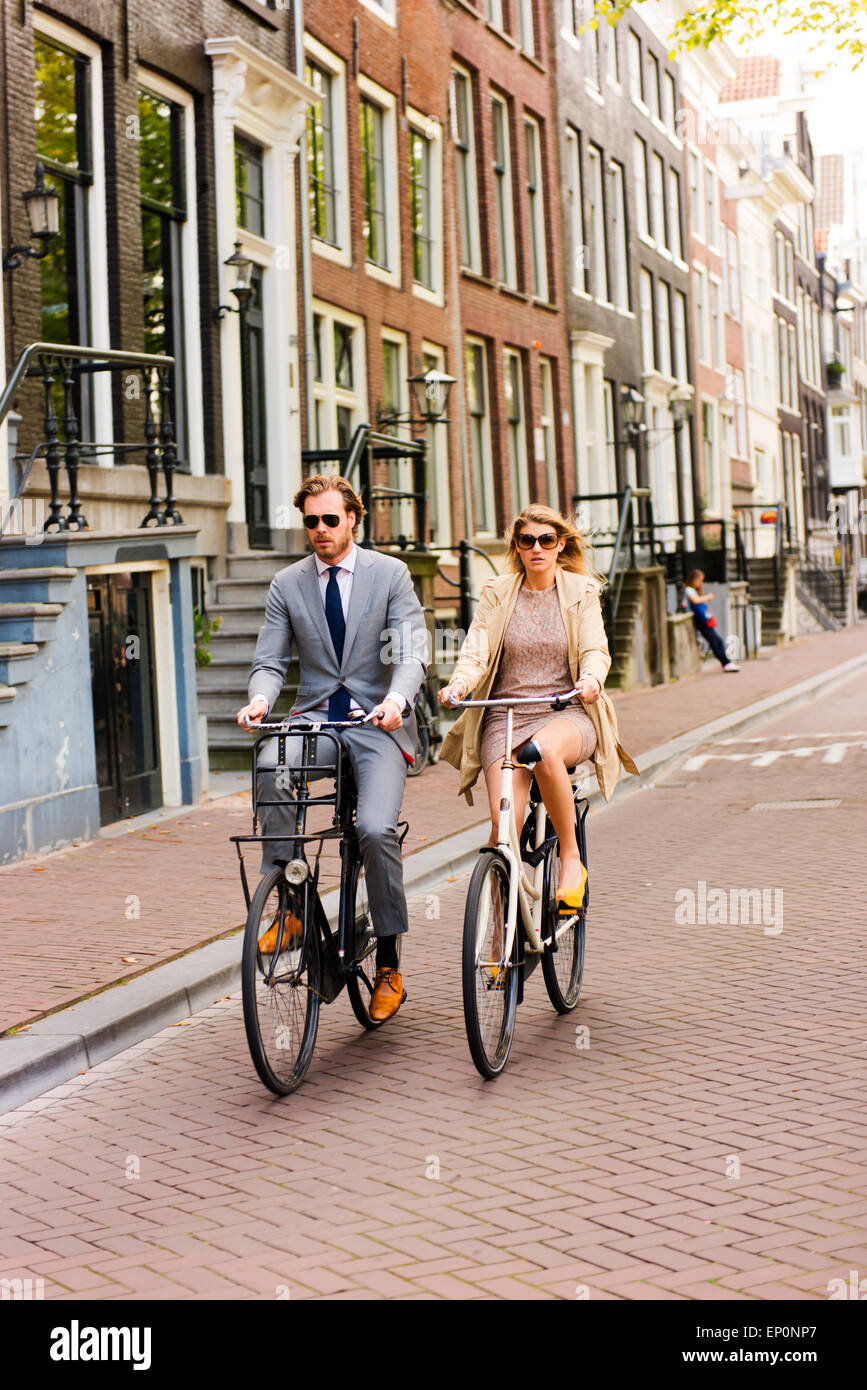Couple riding their bicycles to a formal event. Stock Photo