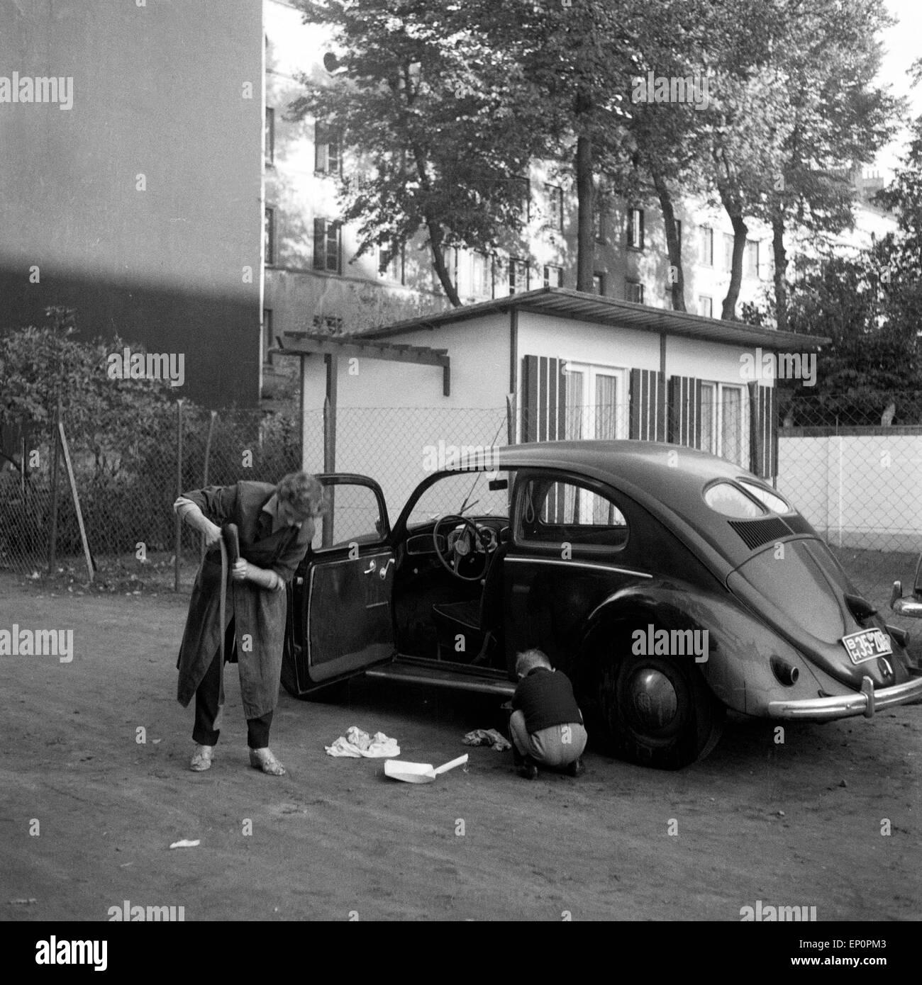 Der beliebte VW Käfer mit Brezelfenster wird von der Familie einer Wäsche unterzogen, Hamburg 1954. Popular - Stock Image