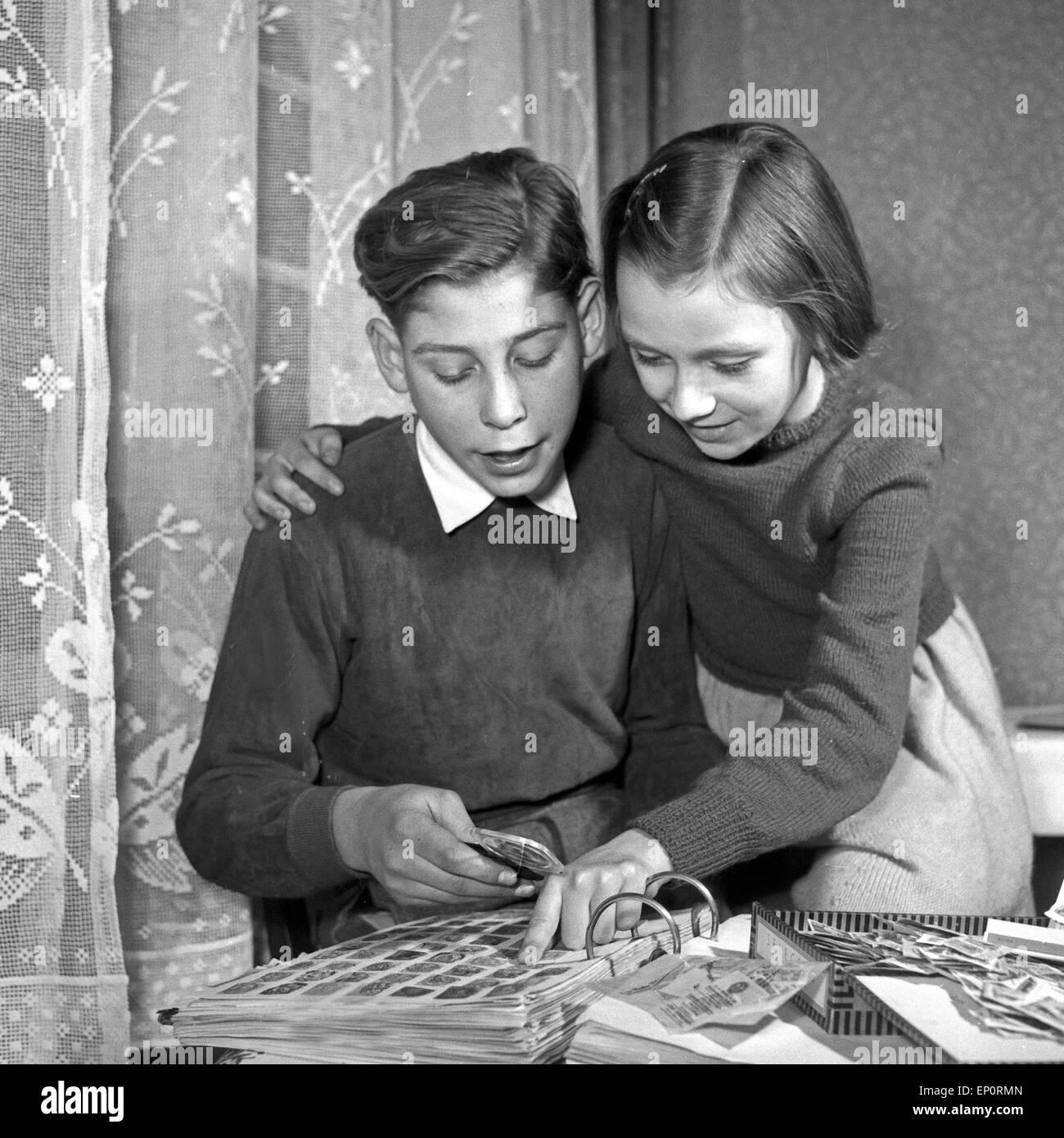 Ein Junge zeigt einem Mädchen seine Briefmarkensammlung, Deutschland 1950er Jahre. A boy showing a little girl his Stock Photo