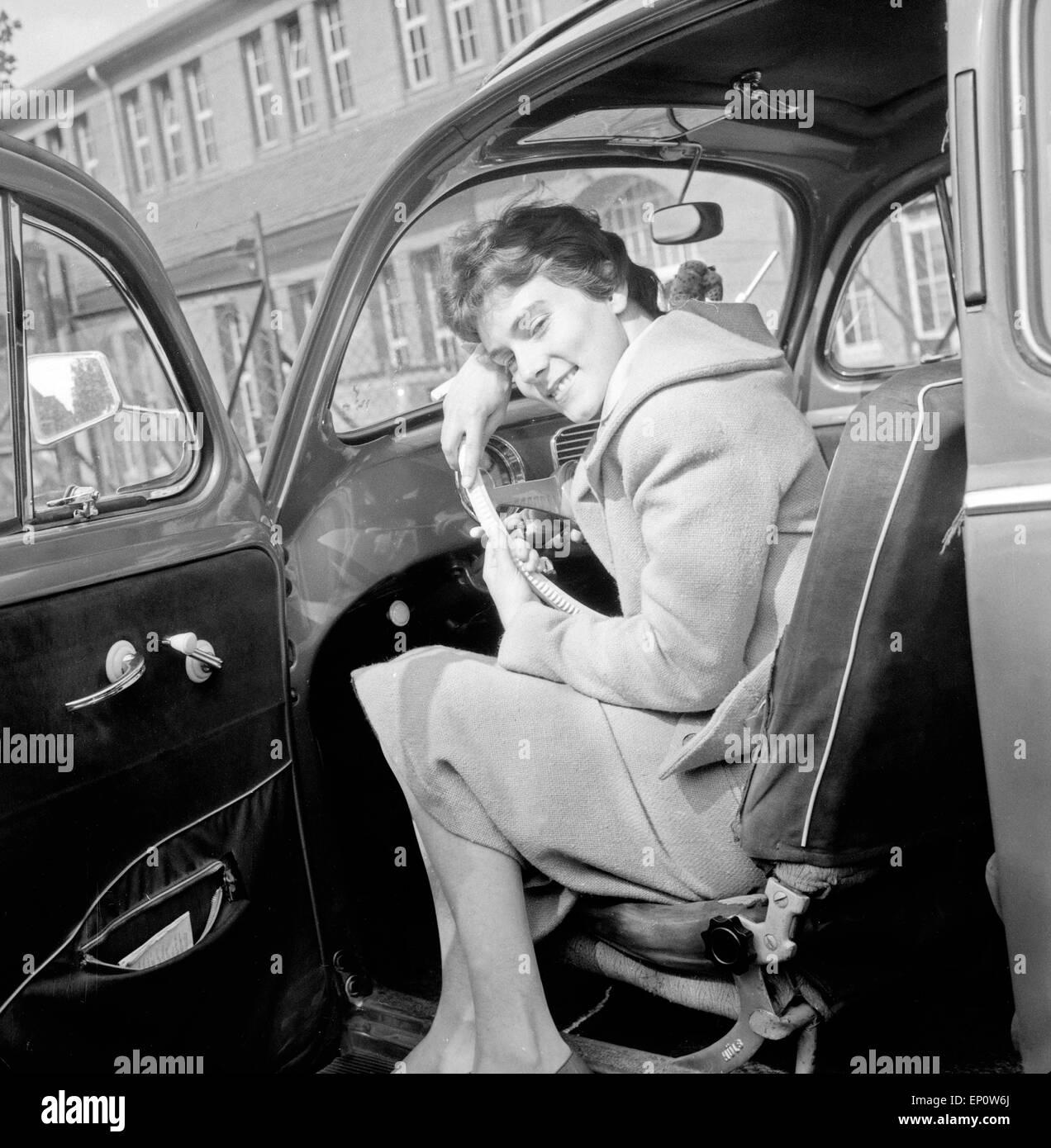 Eine junge Frau an einem VW Käfer in Hamburg, Deutschland 1950er Jahre. A young woman with a Volkswagen beetle - Stock Image