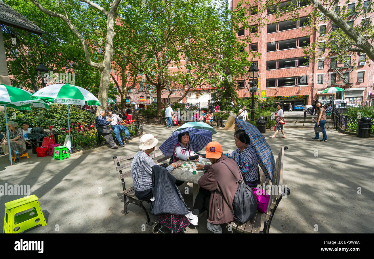 Gambling Chinese women use umbrellas to protect themselves from the sun in Columbus Park in Chinatown in New York - Stock Image