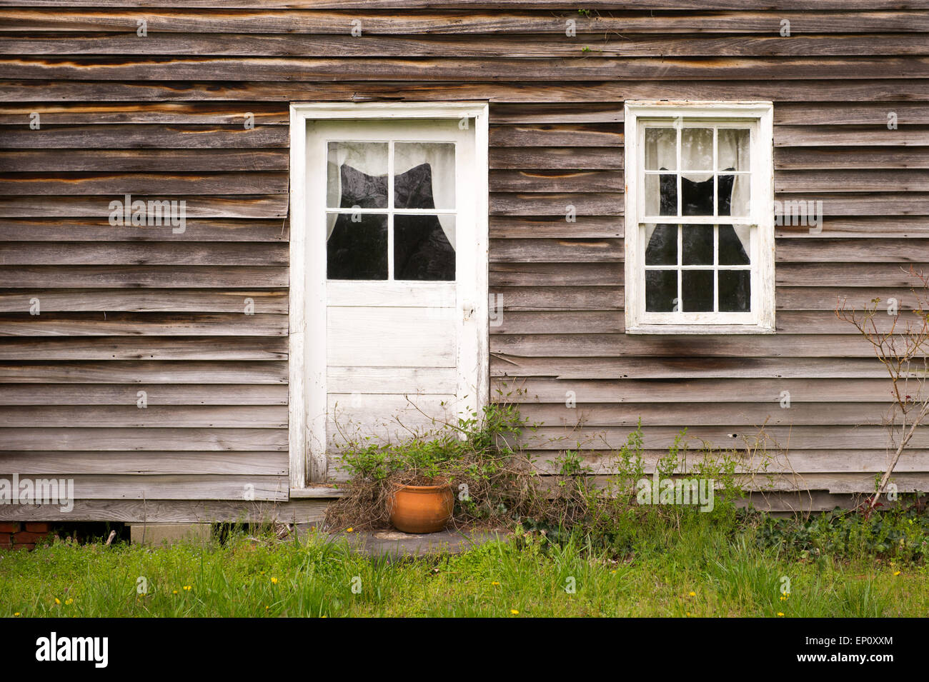 Close-up of house with old wooden siding and white painted door and window in Chrisfield, Maryland - Stock Image
