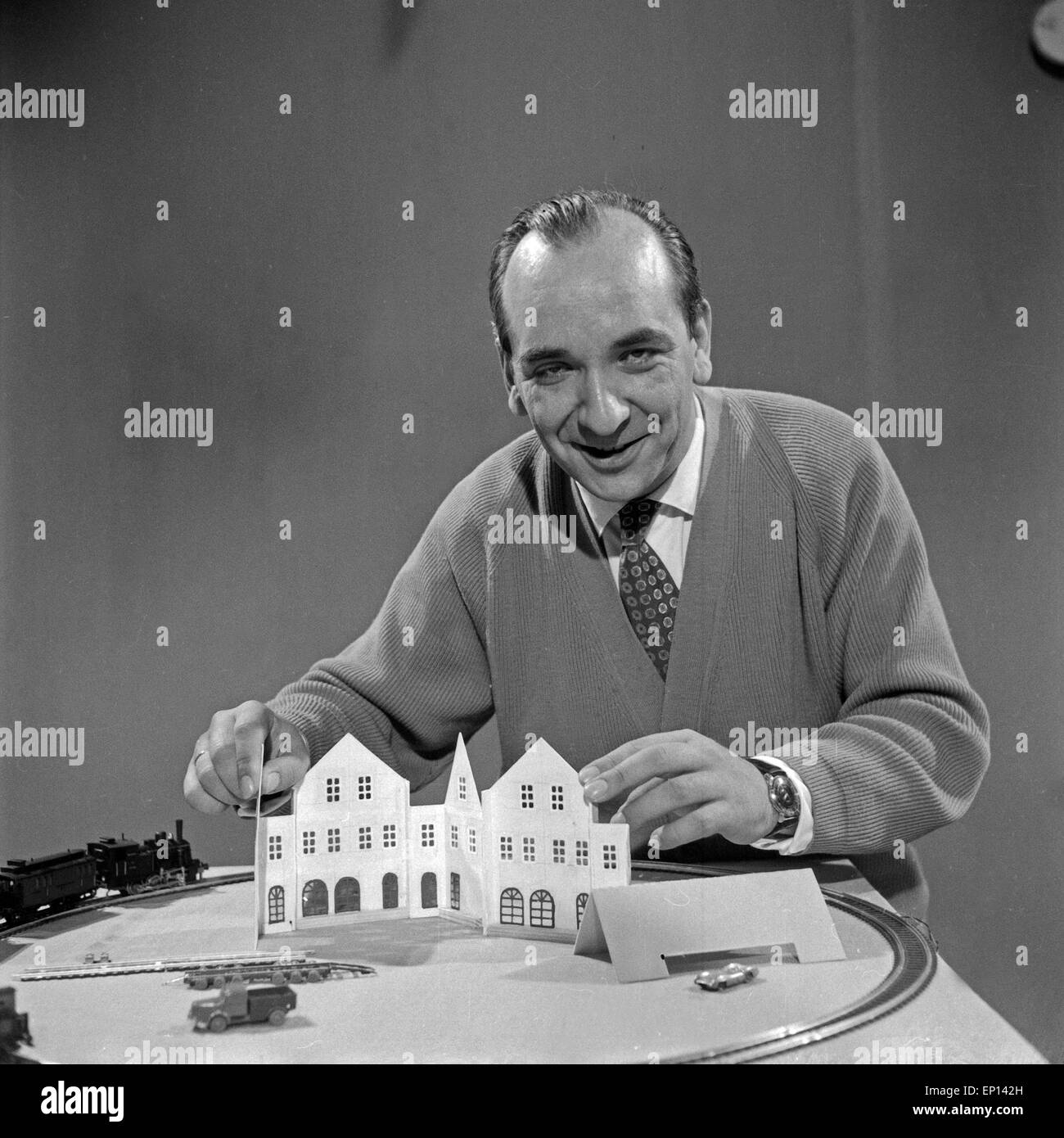 Ein Mann spielt mit seiner Modelleisenbahn, Deutschland 1950er Jahre. A man playing with his model train, Germany Stock Photo