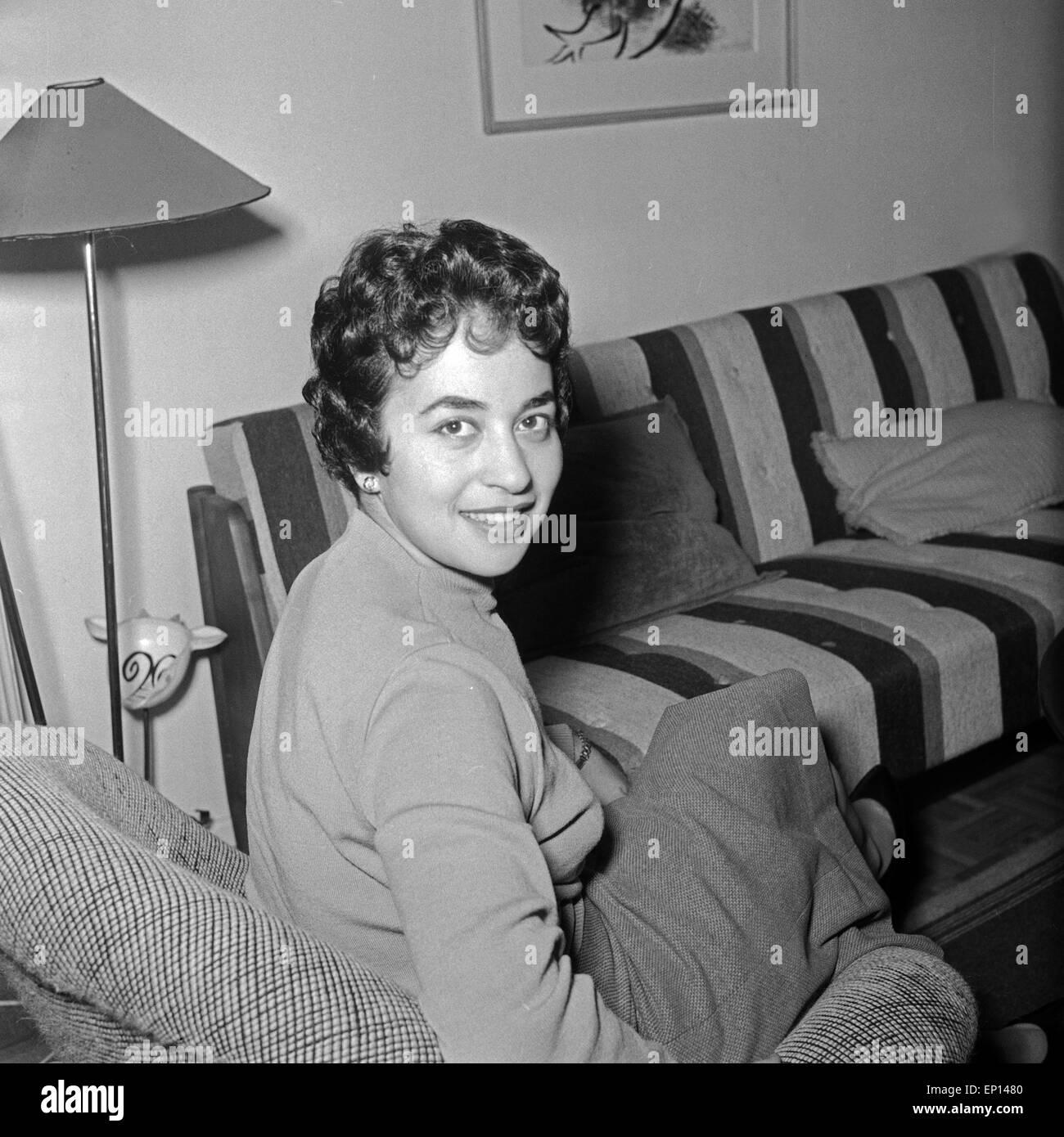 Deutsche sitzt im Wohnzimmer im Sessel, Deutschland 1950er Jahre ...