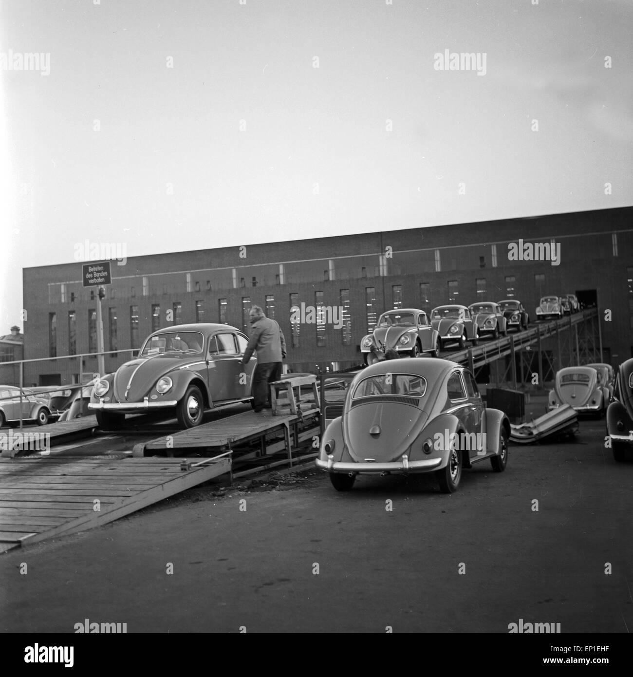 VW Käfer verlassen das Volkswagenwerk in Wolfsburg und werden auf die Eisenbahnrampe verladen, Deutschland - Stock Image