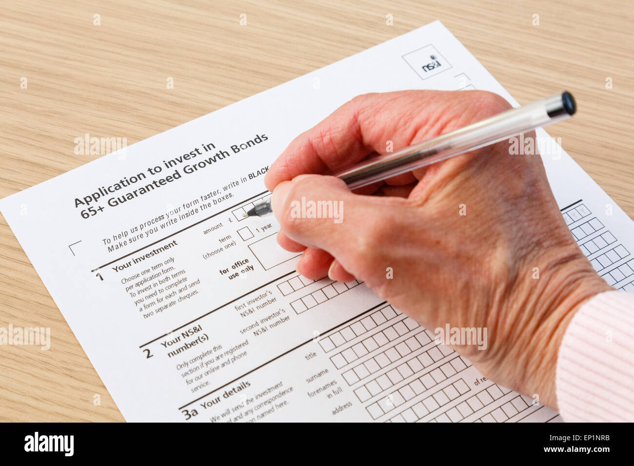 Elderly senior pensioner completing an application form to buy investments in 65+ Guaranteed Growth Bonds. England - Stock Image