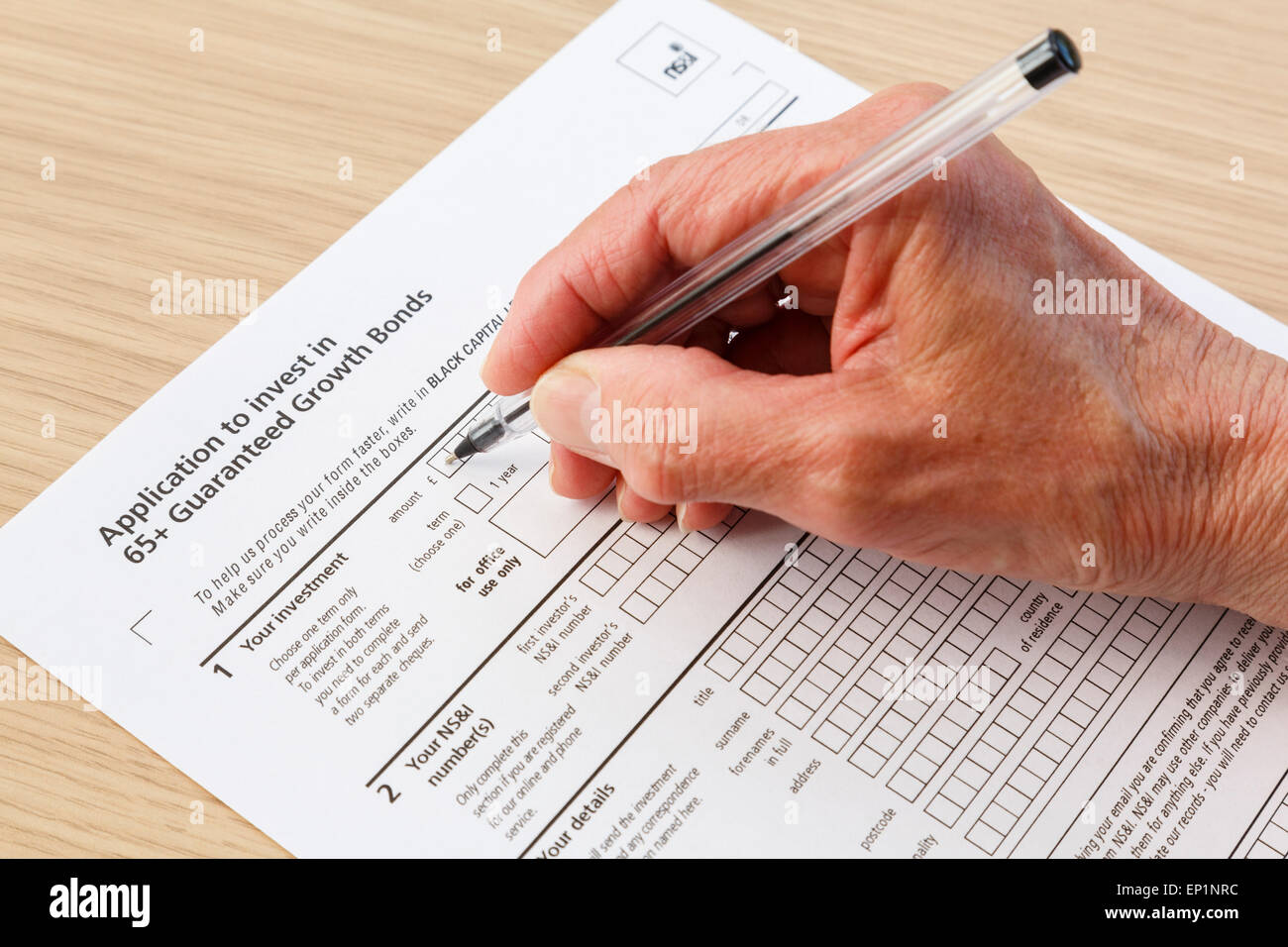 Elderly senior pensioner completing an application form to buy investments in 65+ Guaranteed Growth Bonds in black - Stock Image