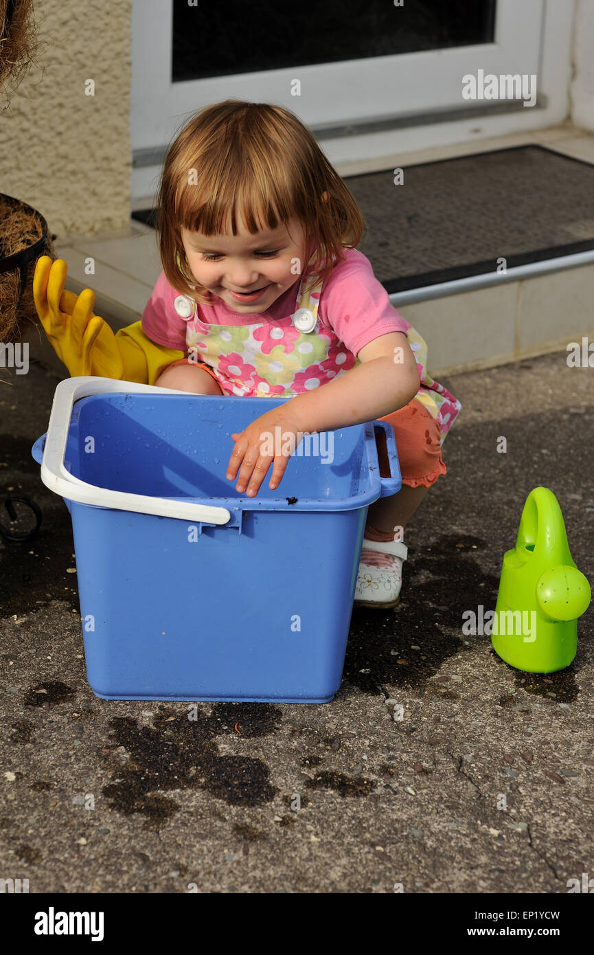 Girl crouching next to a bucket ready to clean - Stock Image