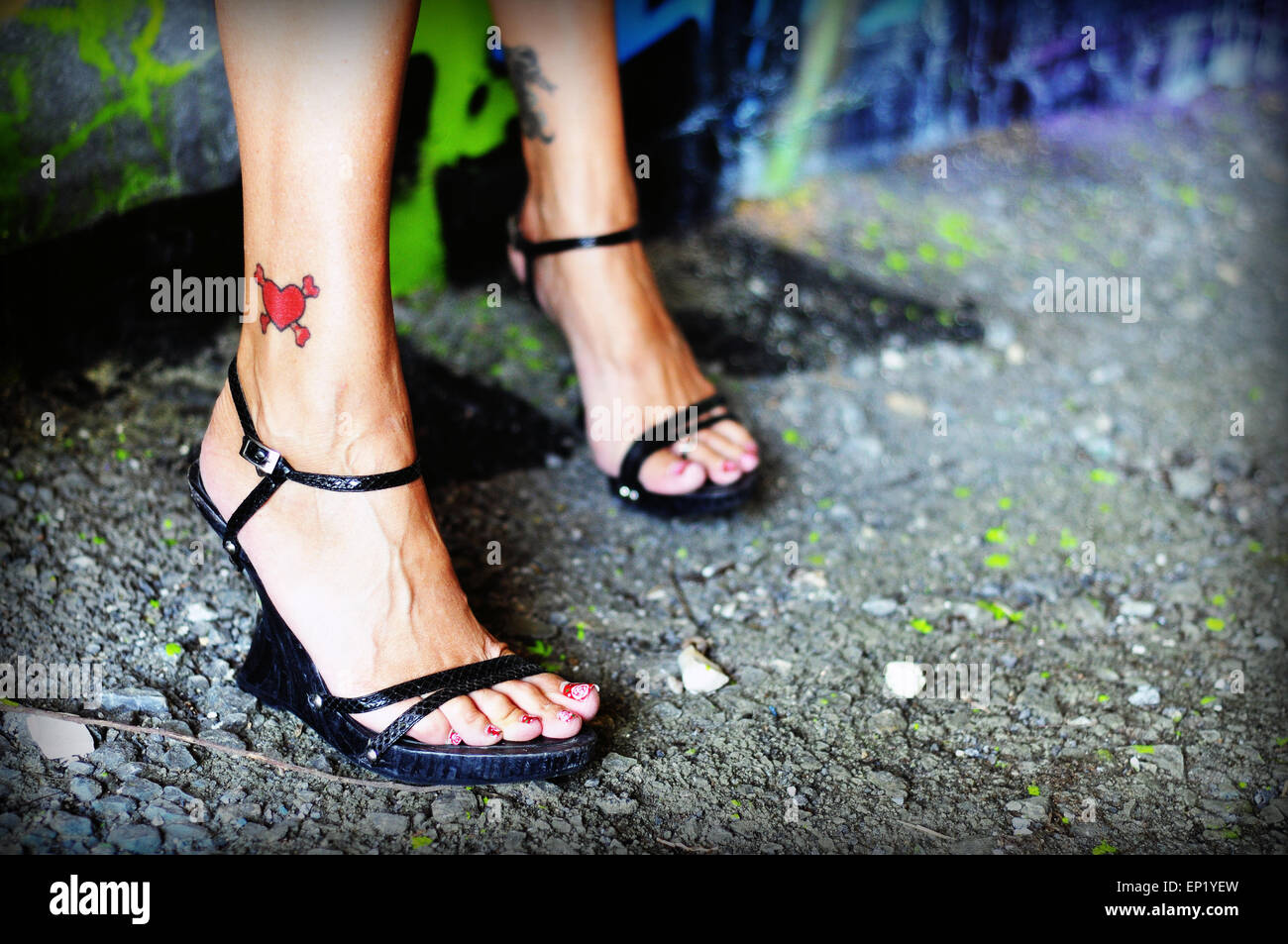 A woman wearing high heel shoes with a heart tattooed on her ankle - Stock Image