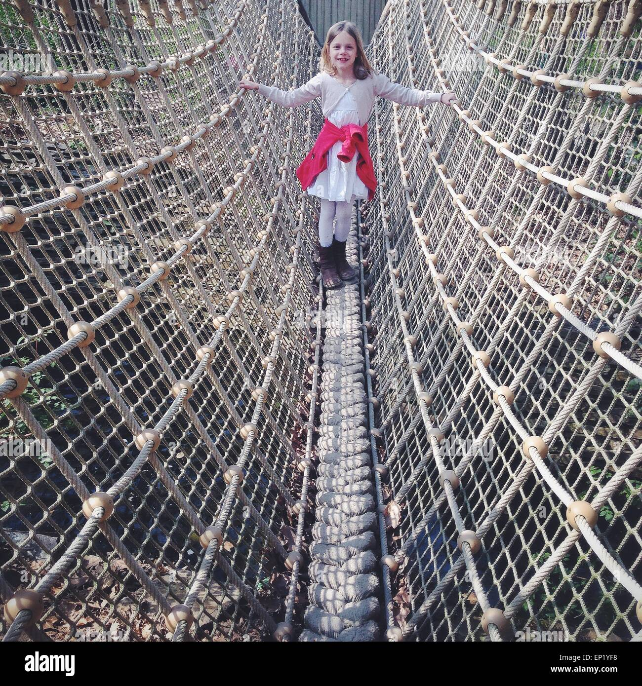 Girl standing on a rope bridge - Stock Image
