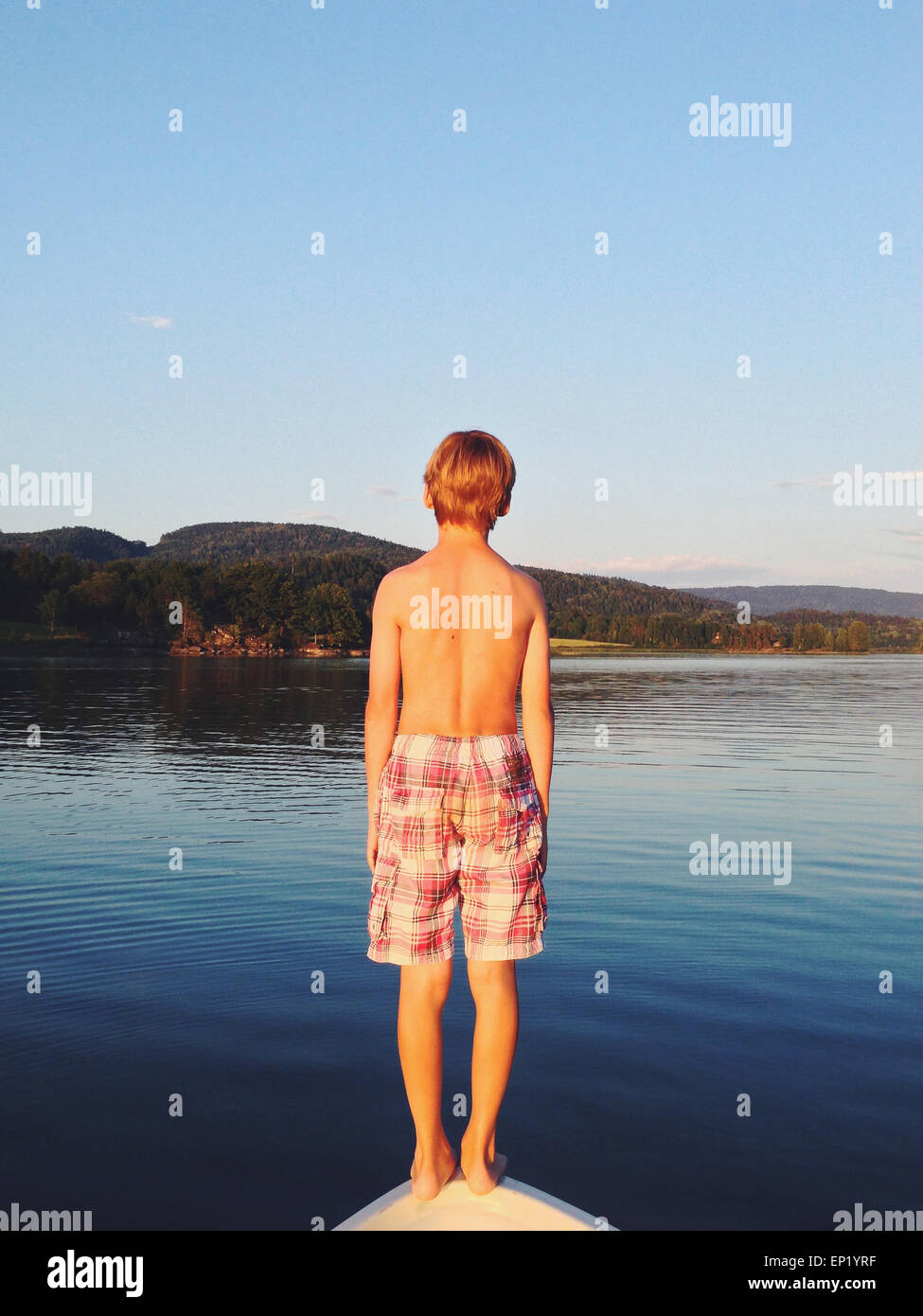 Rear view of a boy standing on bow of a boat ready to jump into the sea, Hof, Norway - Stock Image