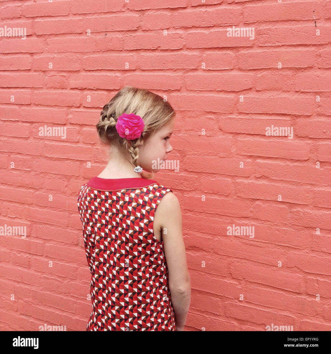 Side view of a girl with a plait and a flower in her hair - Stock Image