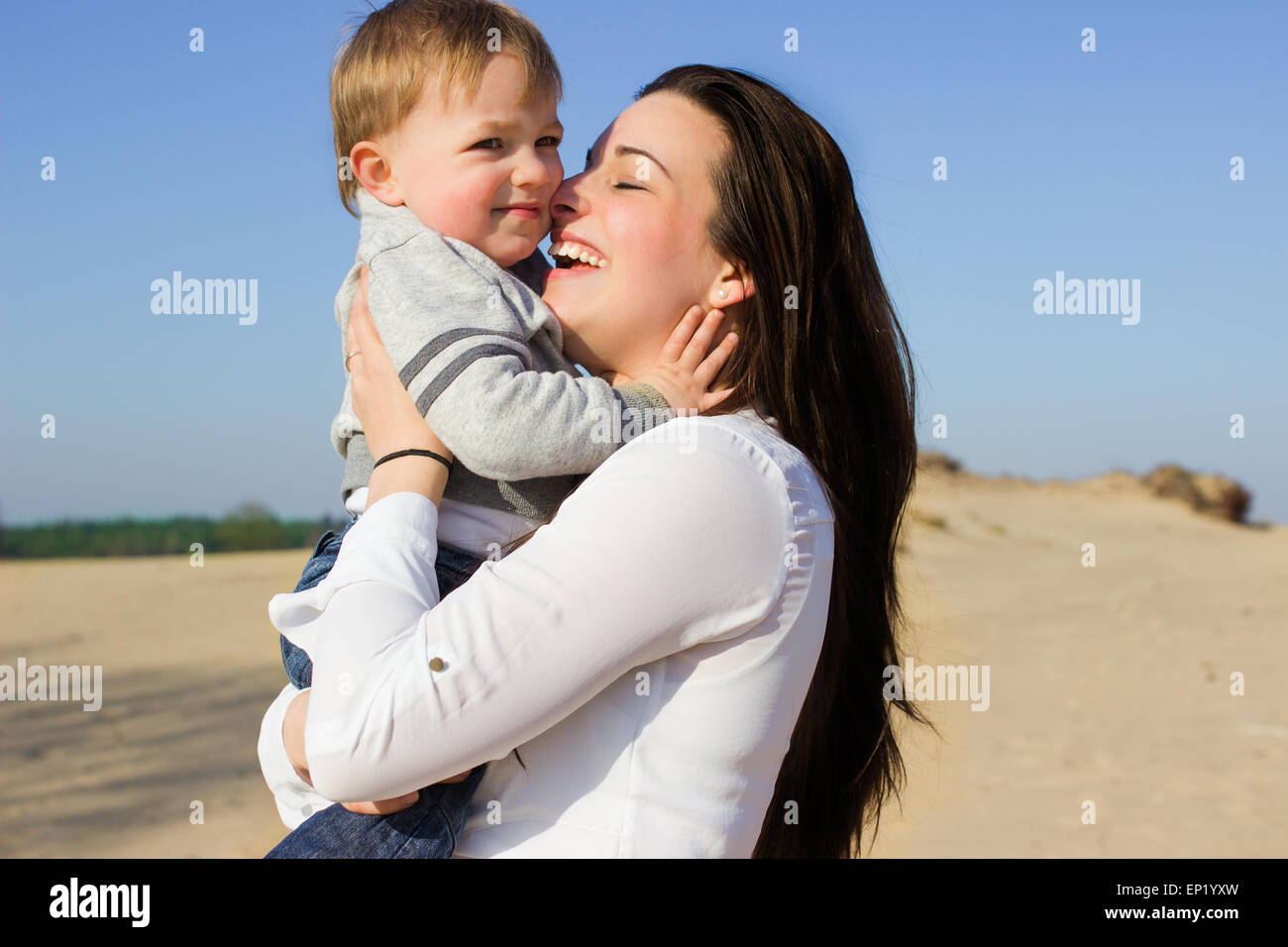Side view of a woman holding her son - Stock Image