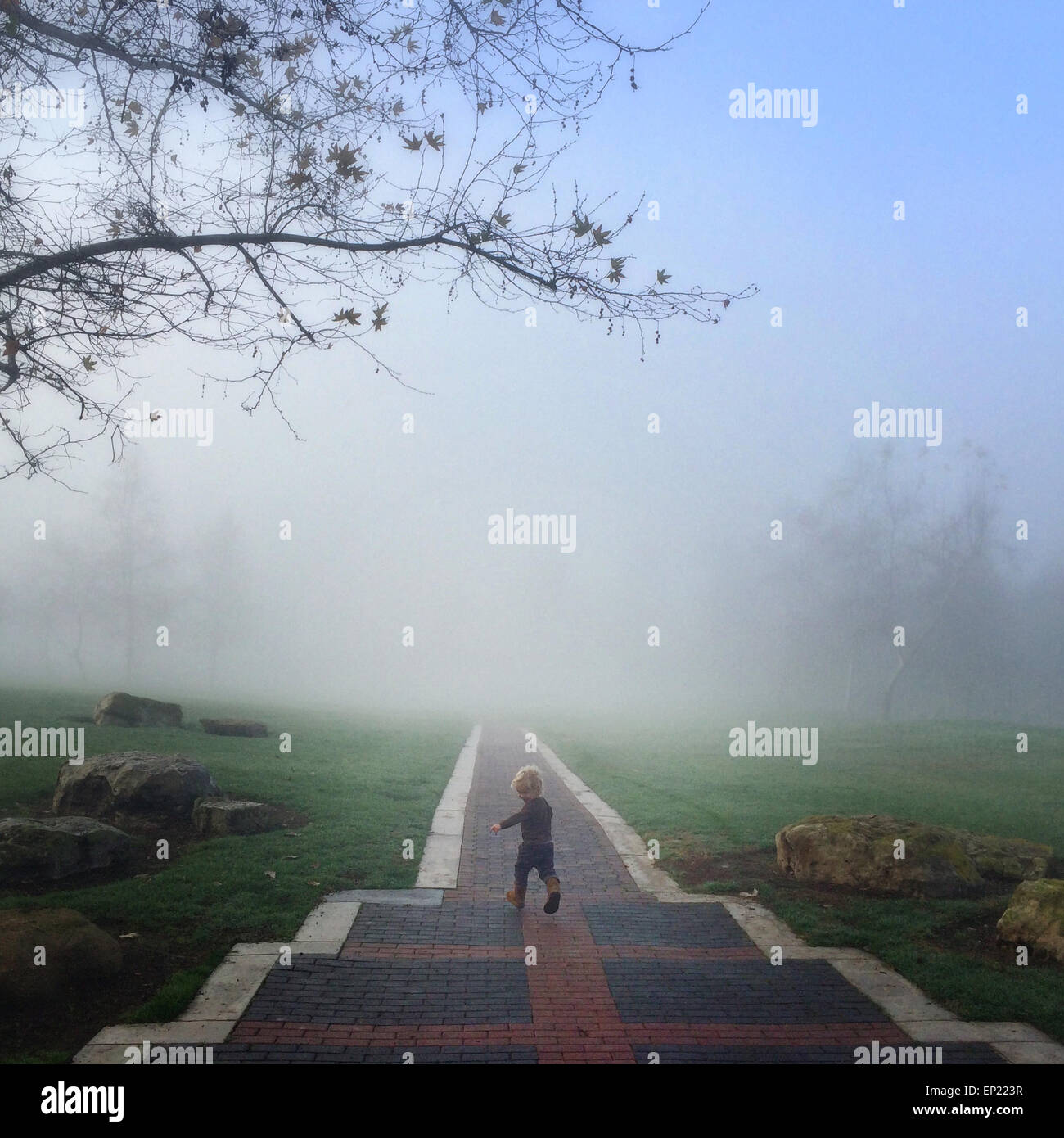 Boy running down path laughing - Stock Image