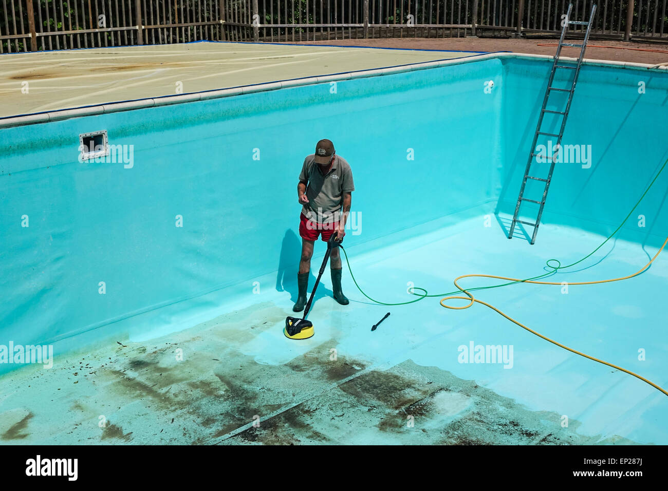 Karcher pressure washer power jet wash patio attachment being used by middle aged man wearing shorts to clean swimming - Stock Image