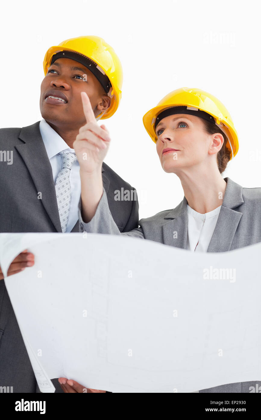 Business people wearing hard hats are talking - Stock Image