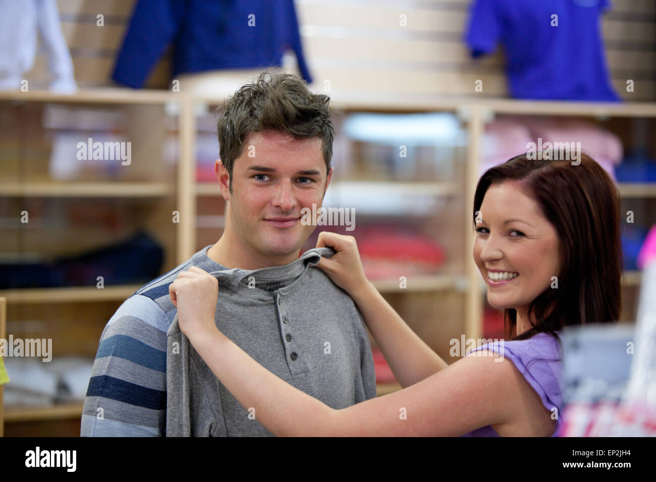 cute woman choosing clothes for her boyfriend in a shop - Stock Image