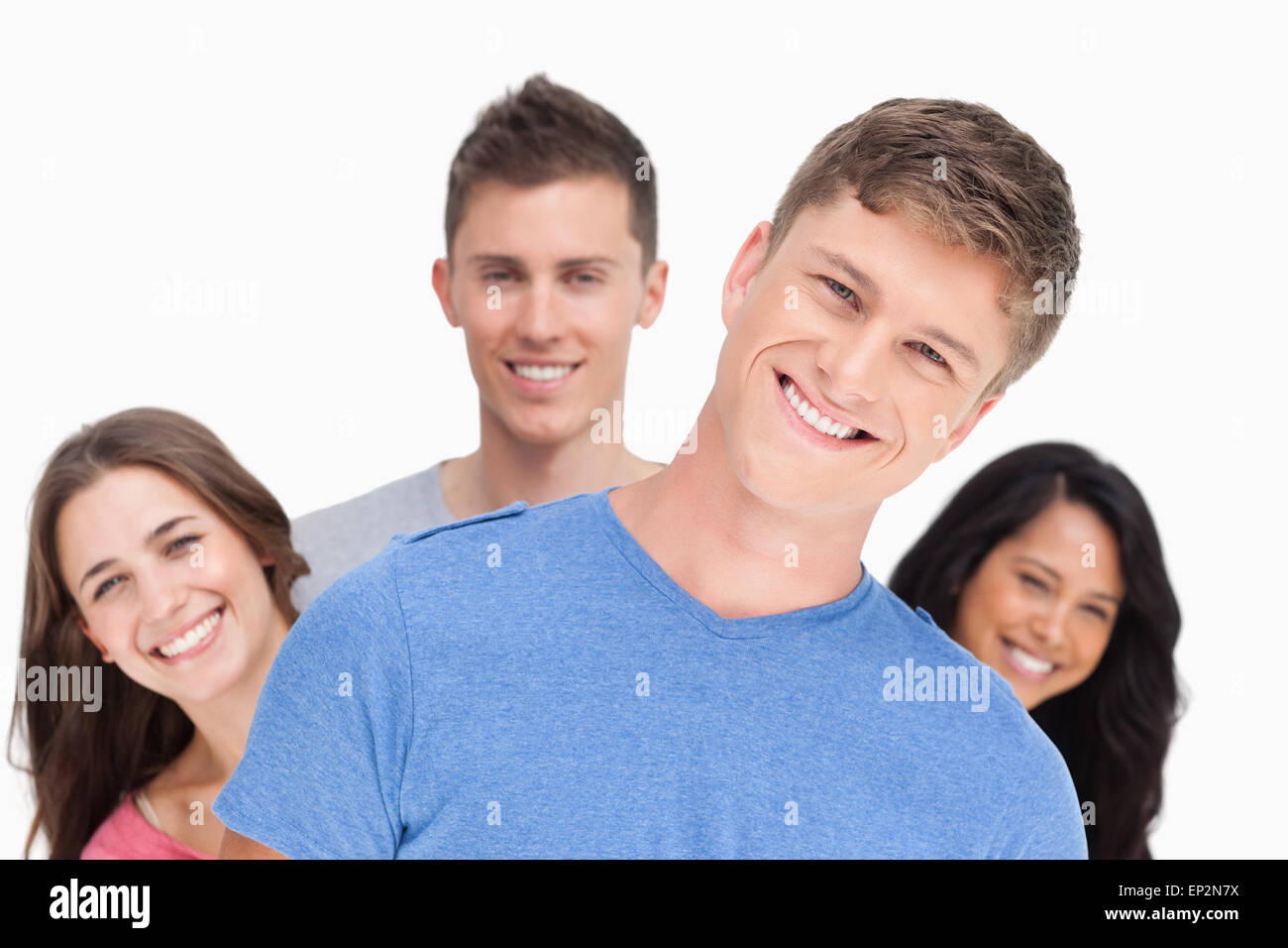A man smiling with his head tilted and his friends behind him - Stock Image
