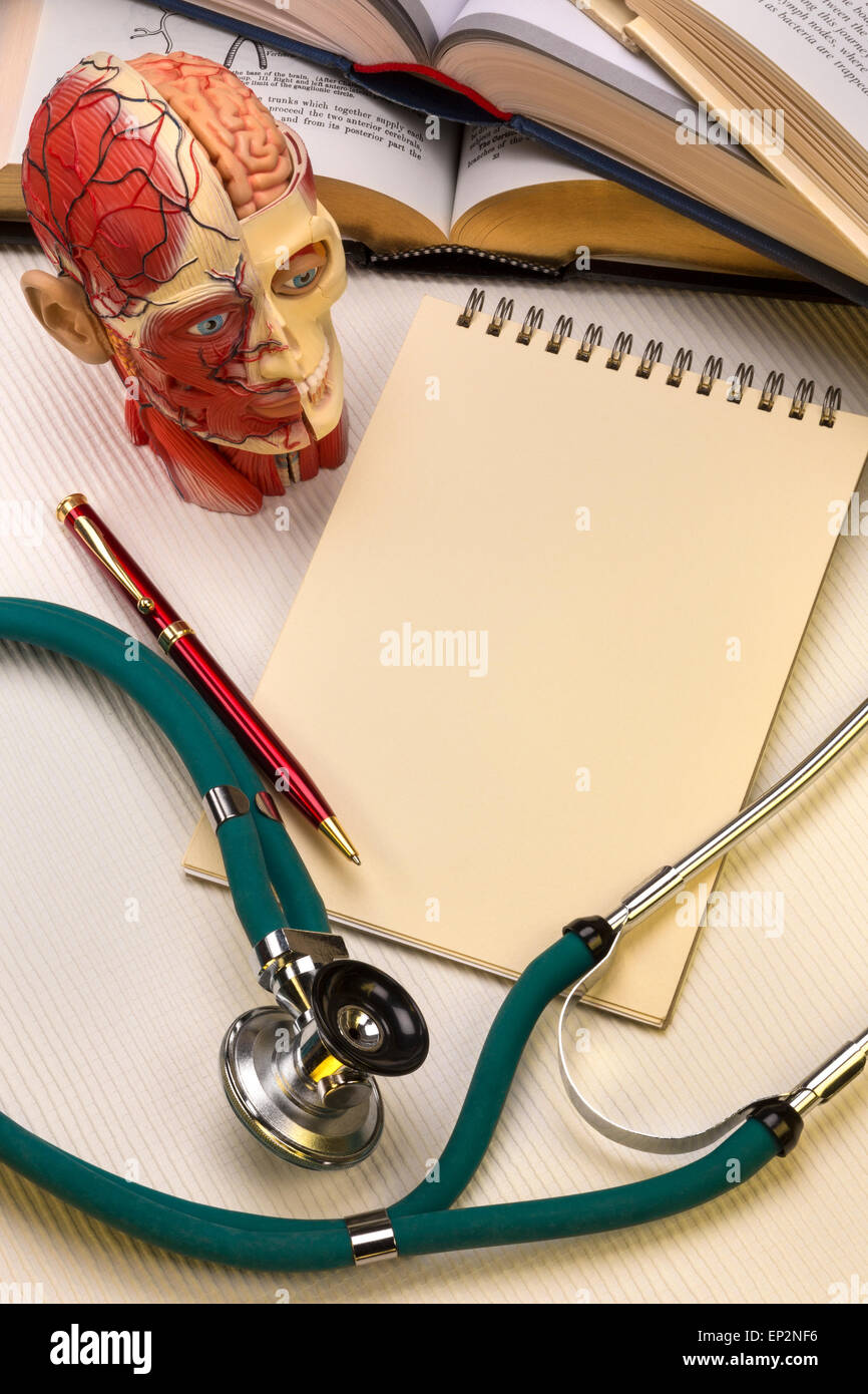 Medical school - A notepad and pen with a medical students stethoscope, medical textbooks and anatomy model. - Stock Image