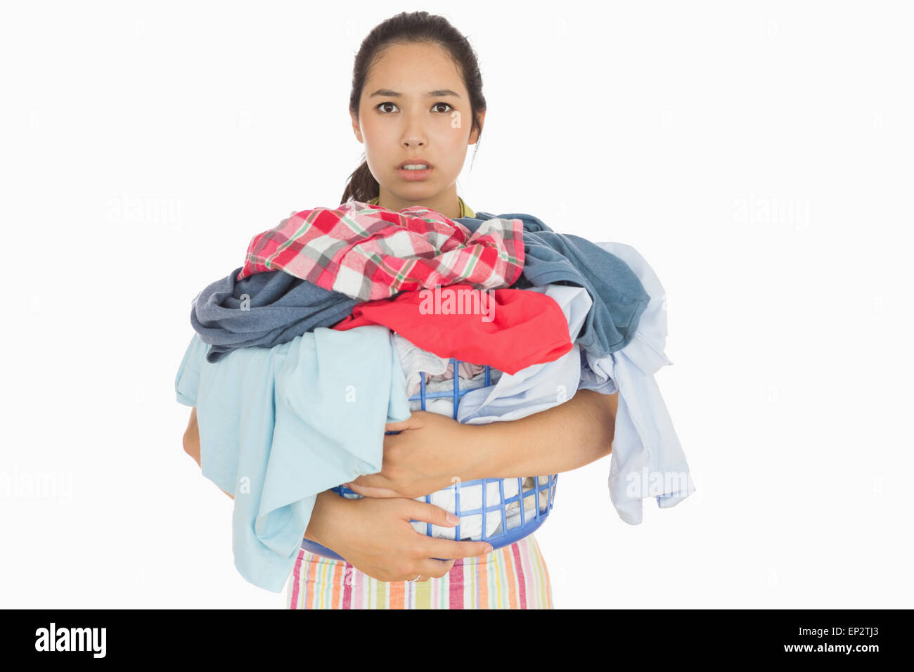 Frowning woman holding basket which is full of dirty laundry - Stock Image