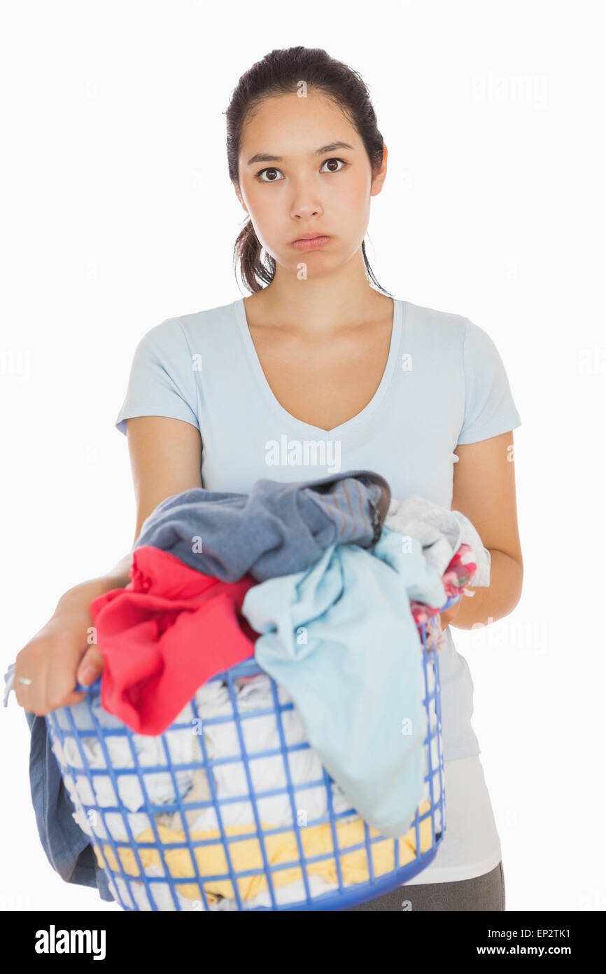 Bored woman holding a basket overflowing of laundry - Stock Image
