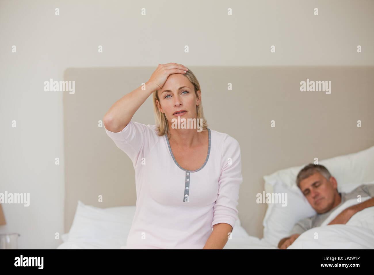 Woman having a headache while her husband is sleeping - Stock Image