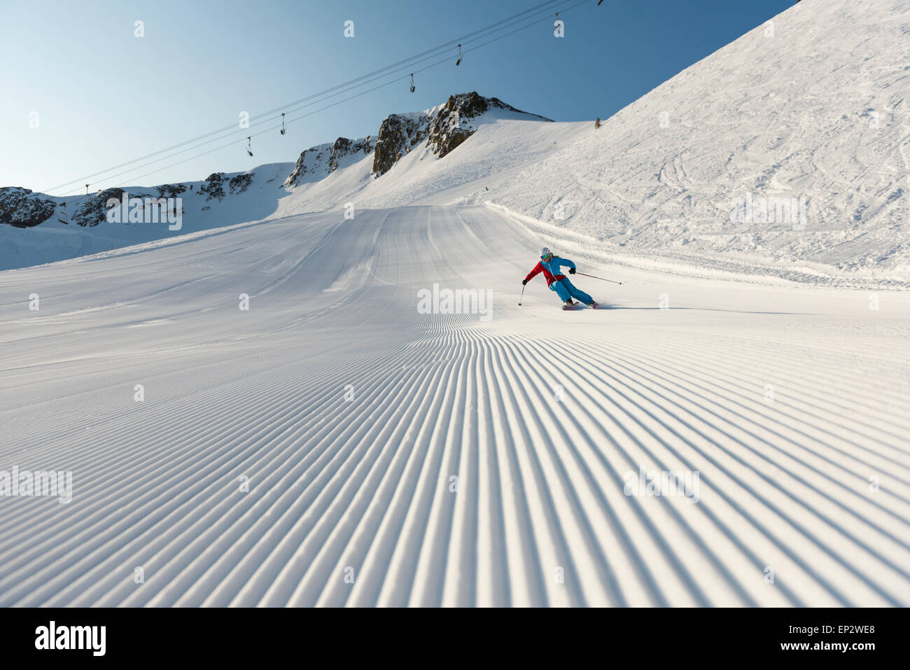 Squaw Valley skier with beautiful groomed snow beneath the palisades on Siberia Lift at Squaw Valley Ski Resort, CA Stock Photo