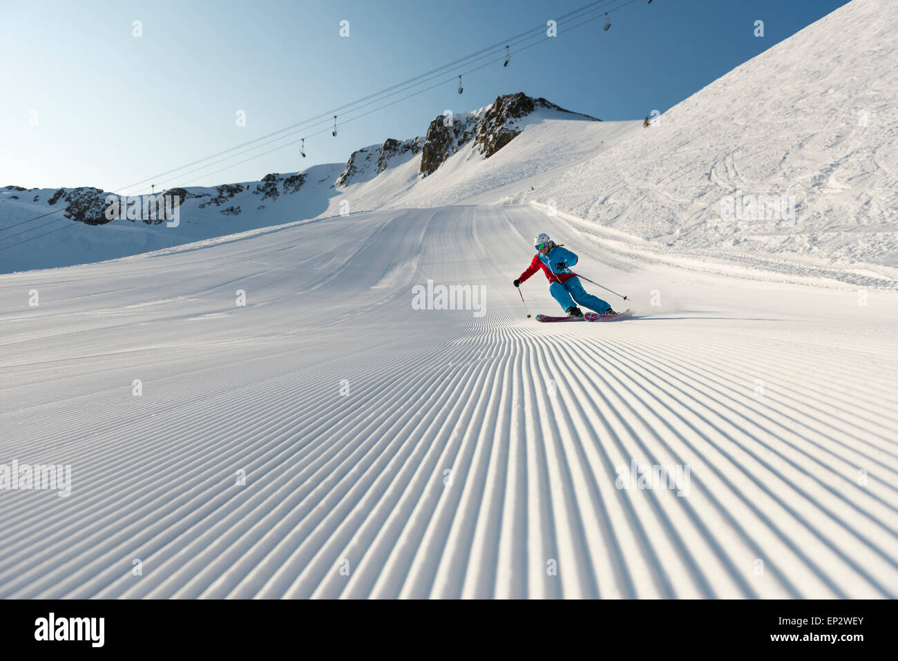 Squaw Valley skier with beautiful groomed snow beneath the palisades on Siberia Lift at Squaw Valley Ski Resort, - Stock Image