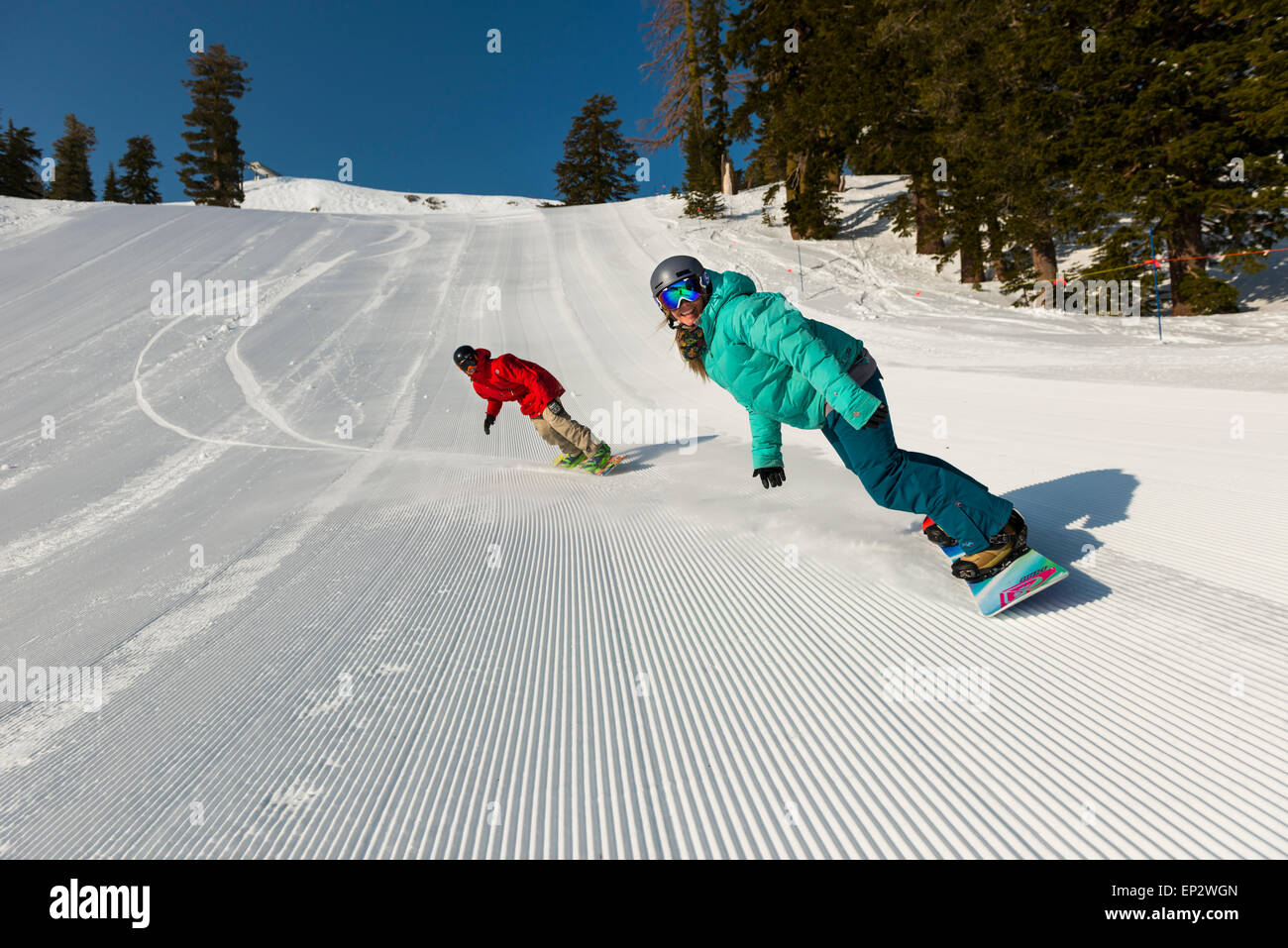 A pair of snowboarders ride perfectly groomed runs on a bluebird spring day at squaw valley, lake tahoe - Stock Image