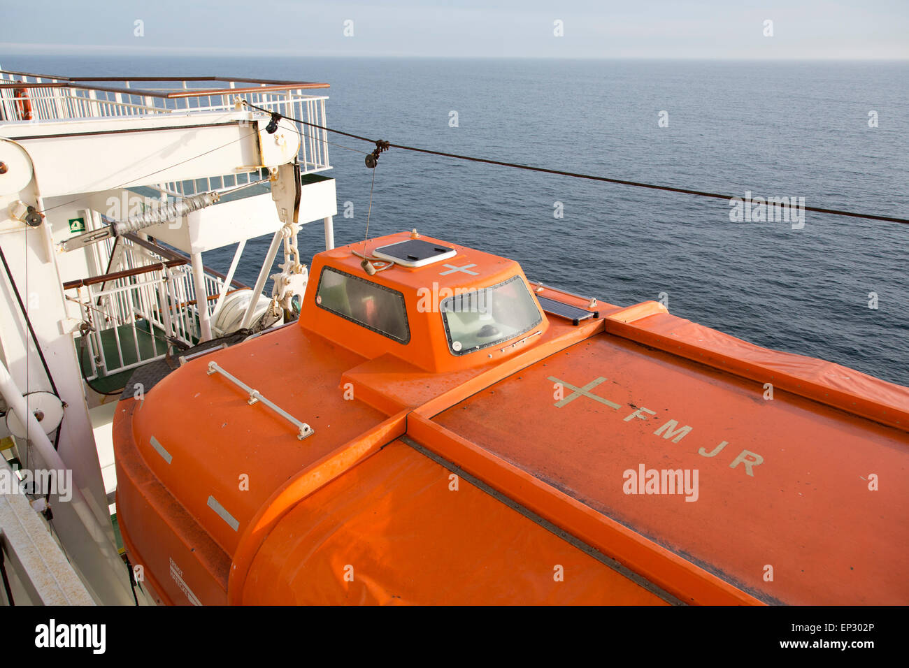 An orange lifeboat attached to the side of a cross channel ferry with the English Channel behind. - Stock Image