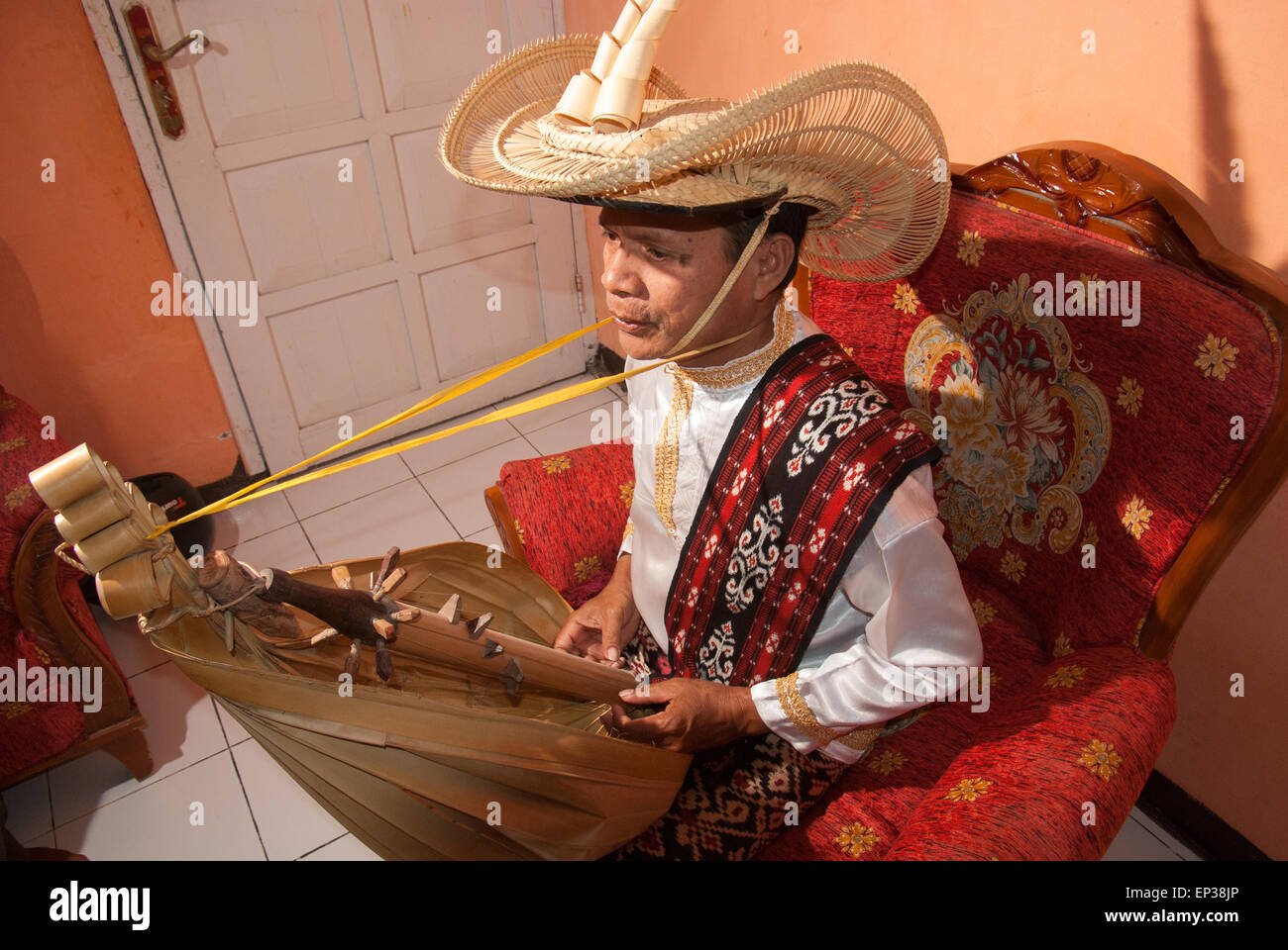 Man wears traditional clothes as he plays sasando music instrument of Rote Island, Indonesia. - Stock Image