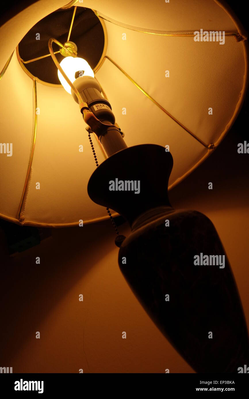 Table lamp in a dark room - Stock Image