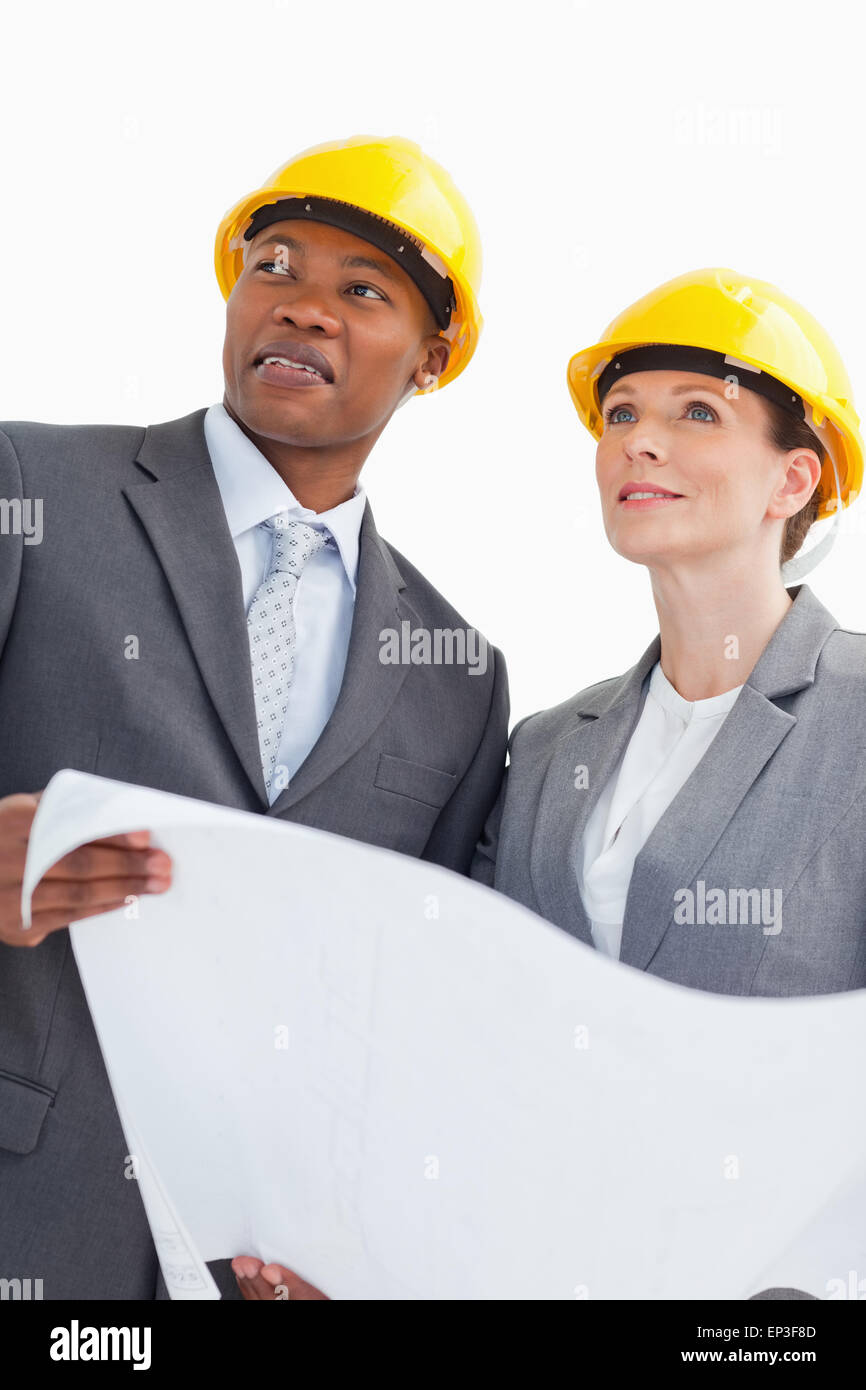 Smiling business people wearing hard hats are holding a paper Stock Photo