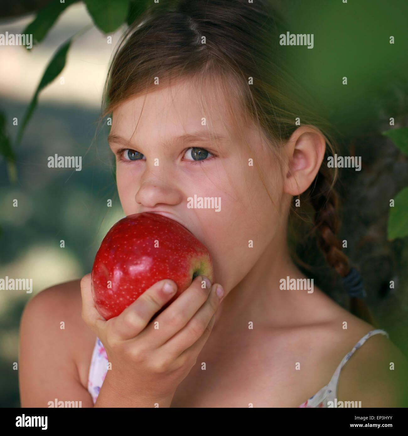 Mädchen beisst in einen Apfel - Stock Image
