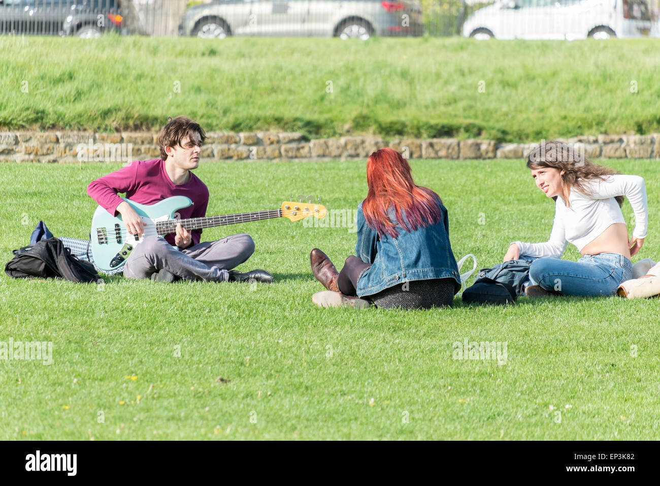 Three student listening and playing music in a park in Bath Somerset - Stock Image
