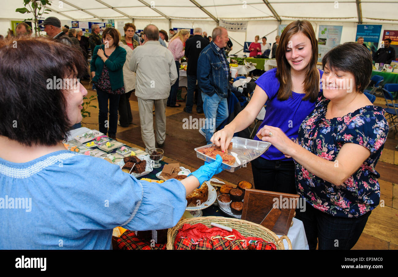 Two woman try a free sample at a Farmers Market - Stock Image