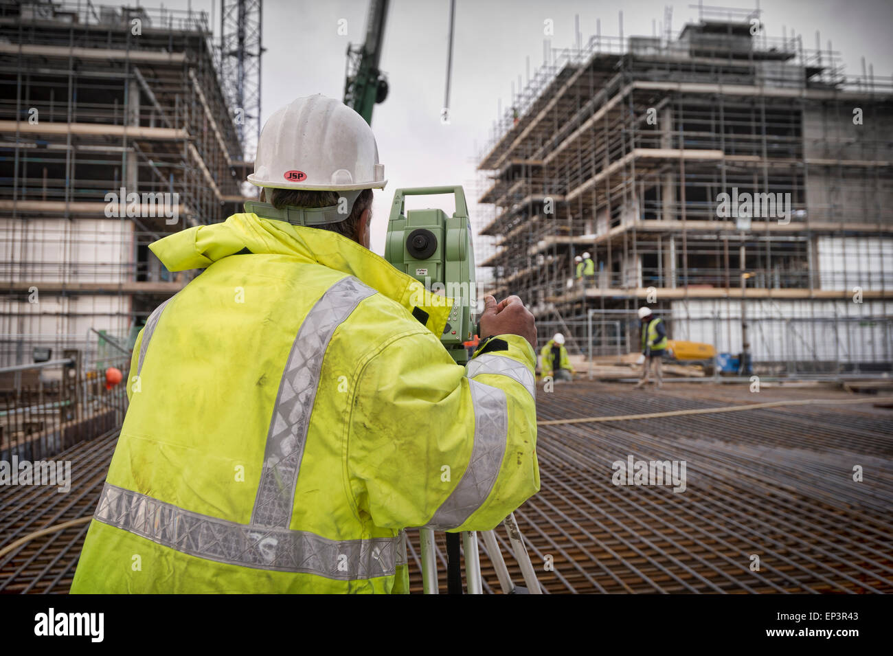 Surveyor on a construction site in yellow High-Viz - Stock Image