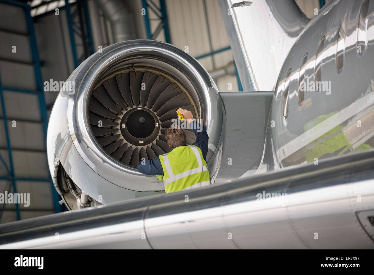 Aircraft mechanic inspecting airplane's jet engine - Stock Image